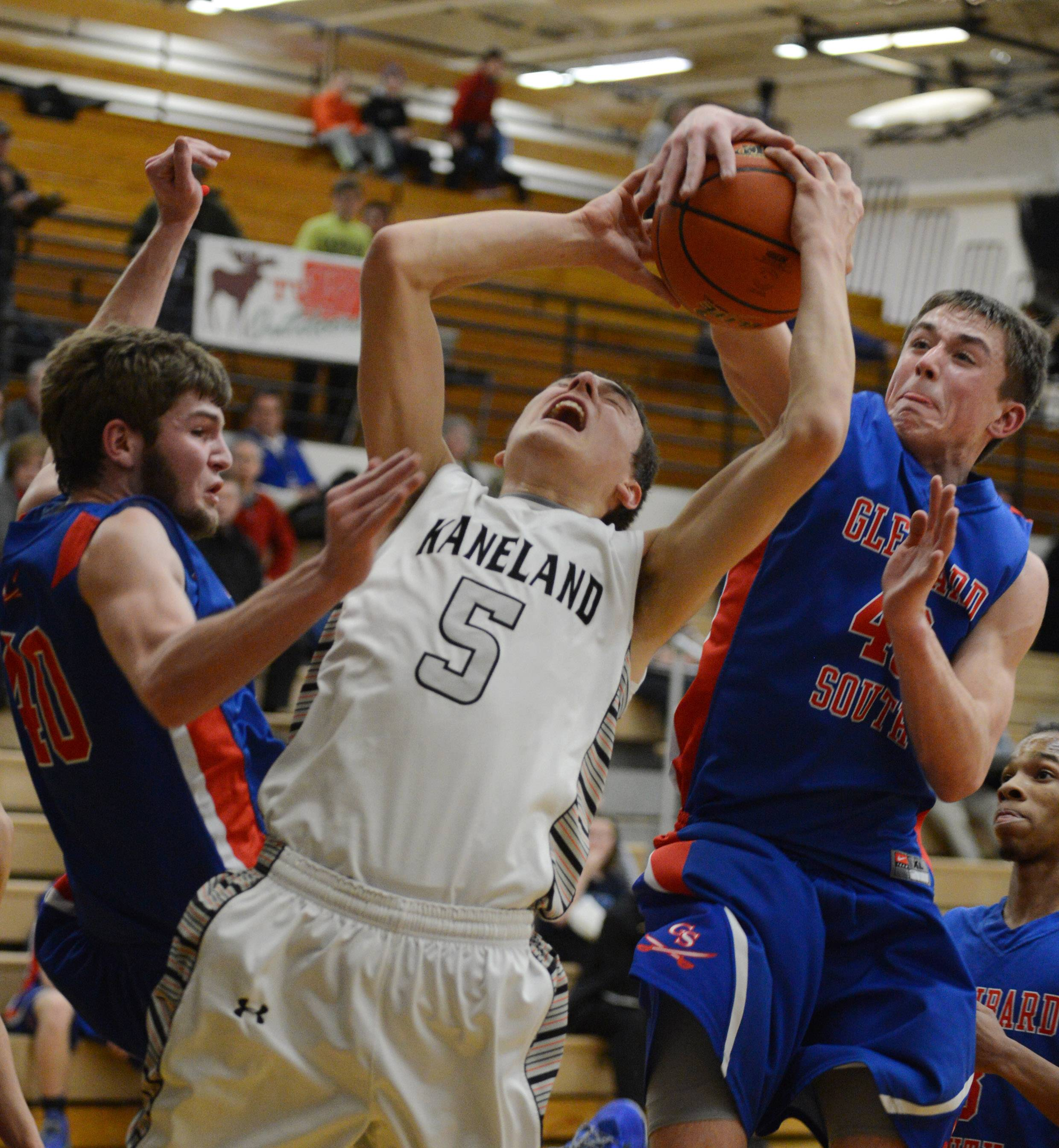 Kaneland's John Pruett is fouled by Glenbard South's Billy Bair.