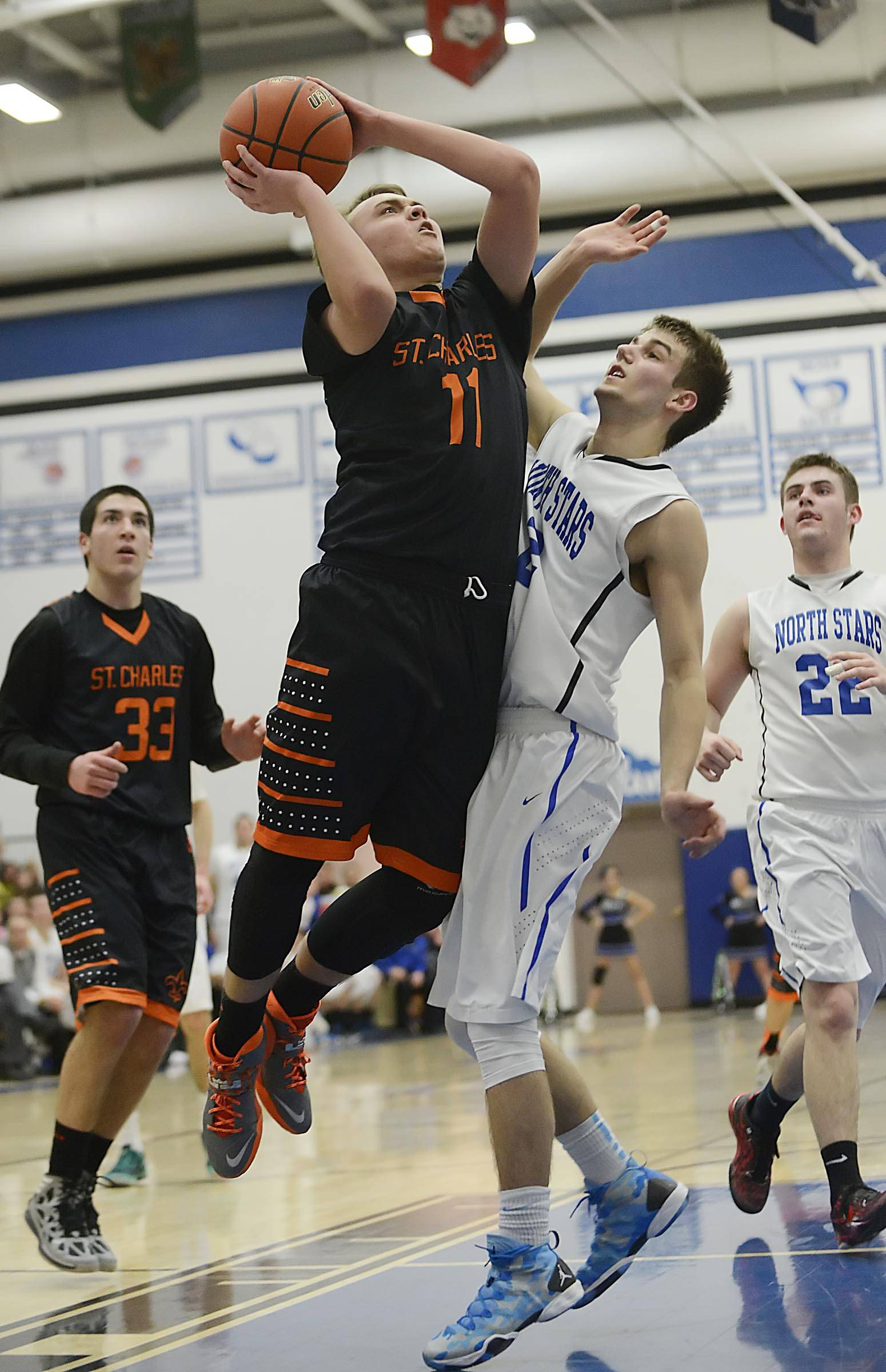 St. Charles East's Mick Vyzral puts up a jump shot against St. Charles North's Jake Ludwig Wednesday in the regional game at St. Charles North.