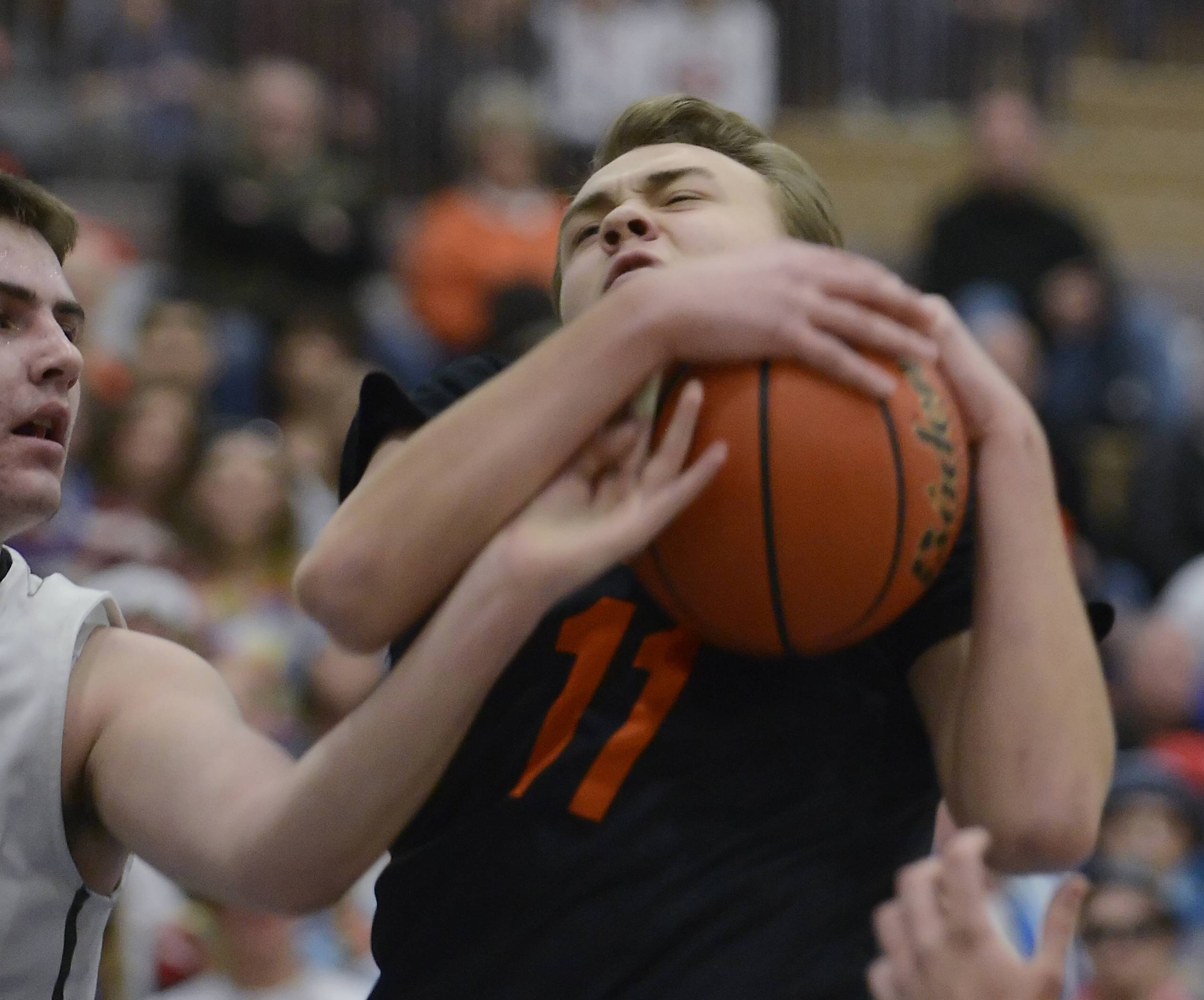 St. Charles East's Mick Vyzral grabs rebound against St. Charles North's Jack Callaghan Wednesday in the regional game at St. Charles North.