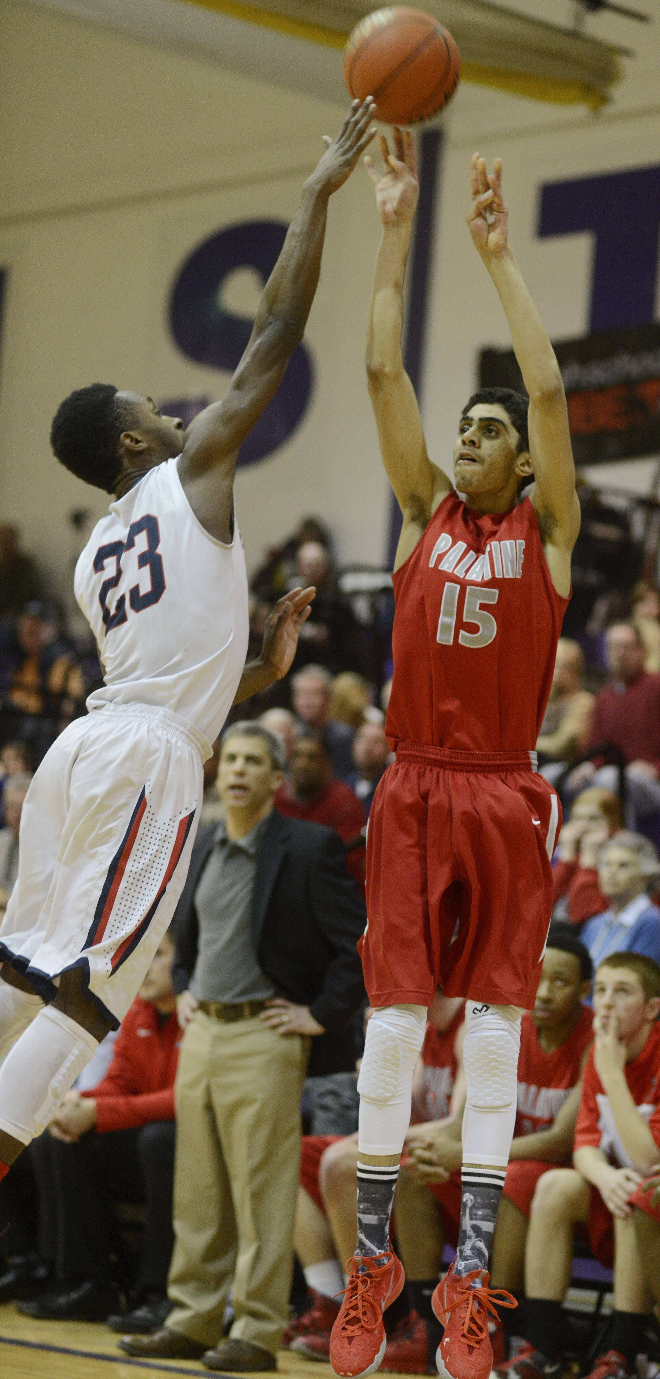 St. Viator's Ore Arogundade, left, defends a shot by Palatine's Justin Chaney during Wednesday's regional semifinal at Rolling Meadows.