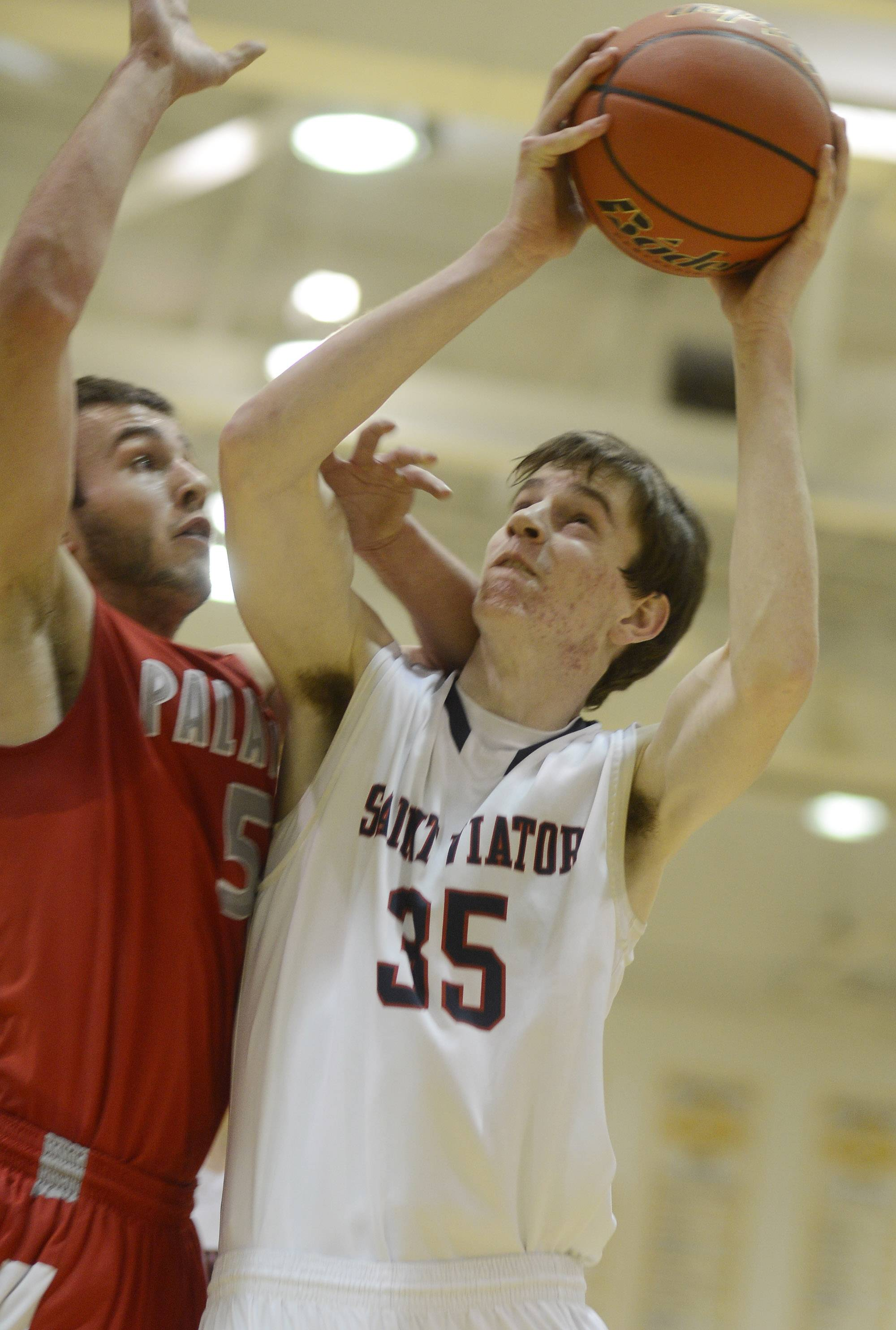 St. Viator's Tom Martin, right, makes a strong move to the basket as he is met by Palatine defender Chris Macahon .