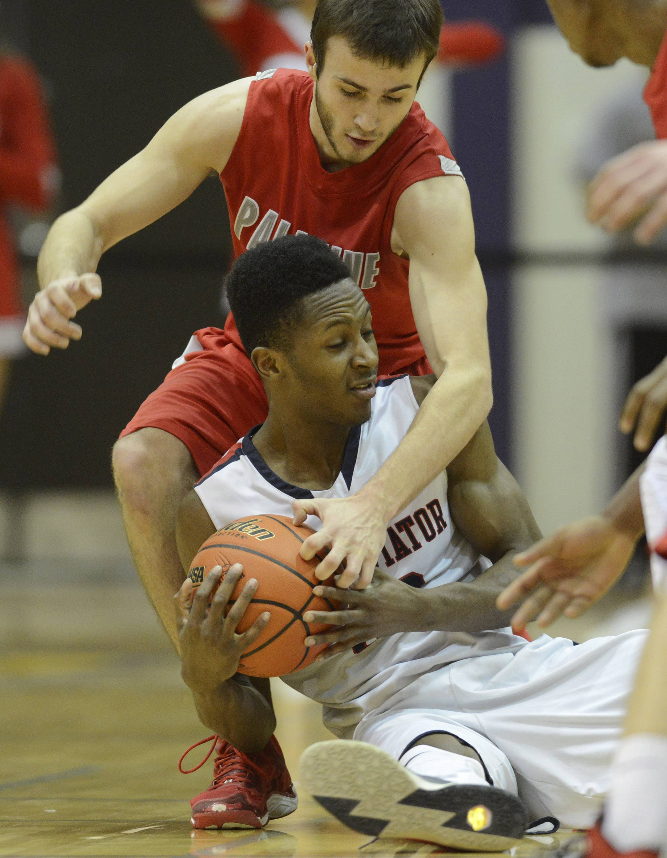 St. Viator's Ore Arogundade, front, keeps the ball from the grasp of Palatine's Chris Macahon.
