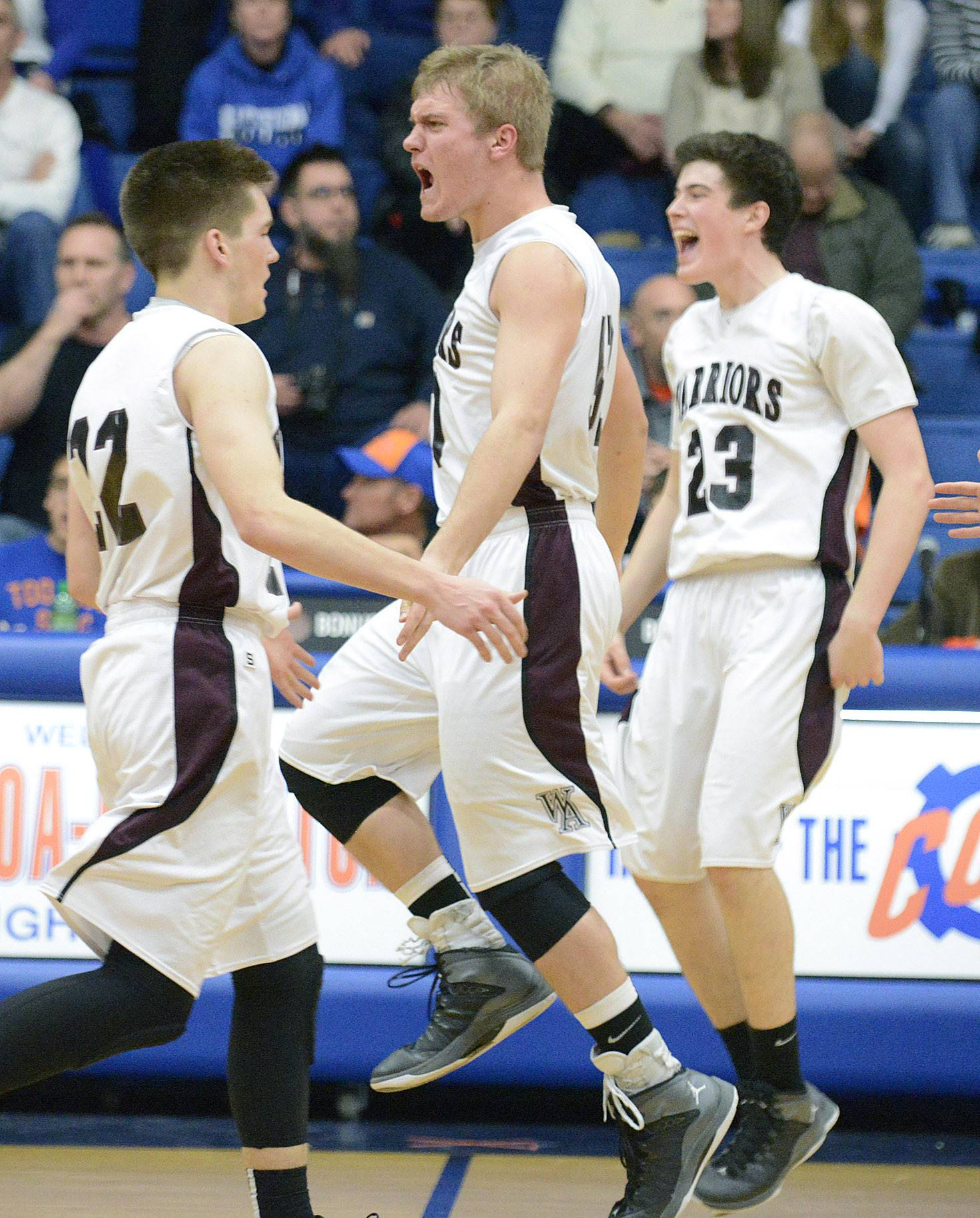 Wheaton Academy's Jacob Lindstedt leaps with excitement onto the court as a time out is called after the Warriors scored to take the lead in the fourth quarter of the Class 3A regional at Genoa-Kingston High School in Genoa on Wednesday.