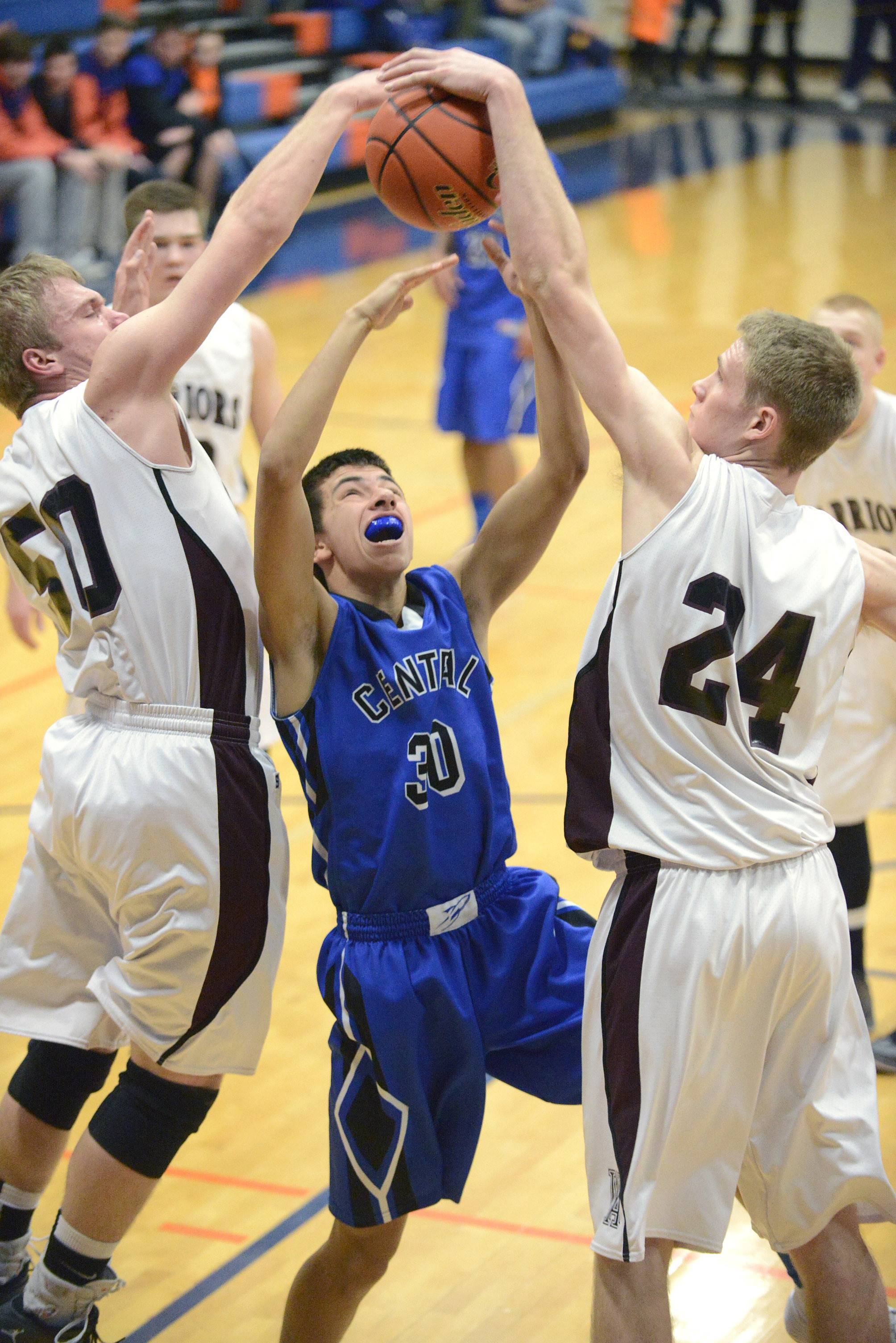 Burlington Central's James Raney is denied a basket by Wheaton Academy's Jacob Lindstedt, left, and Gordon Behr, right, in the second quarter.