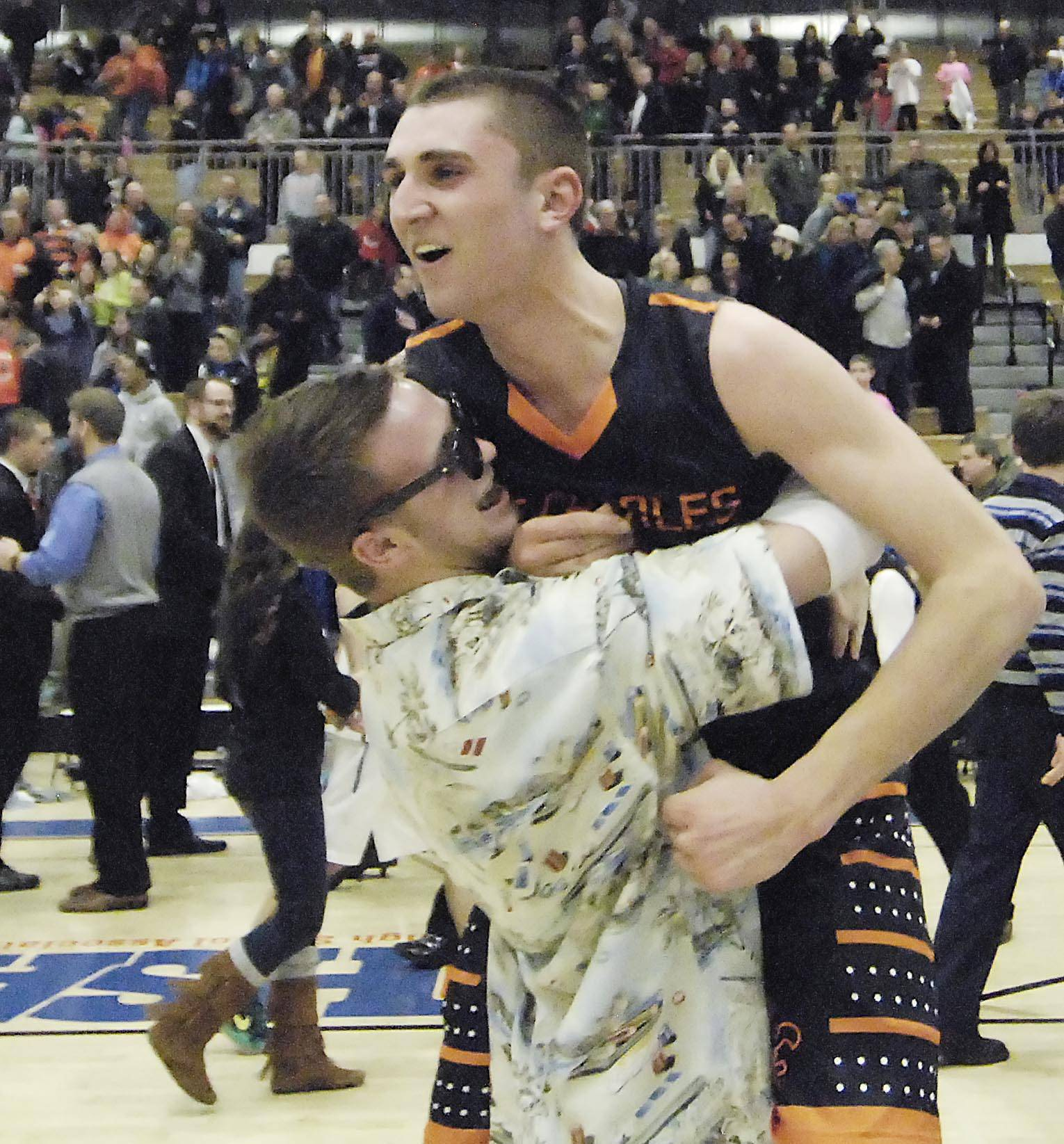 St. Charles East's Dom Adduci is lifted by a classmate Wednesday after the Saints beat St. Charles North in the regional game at St. Charles North.
