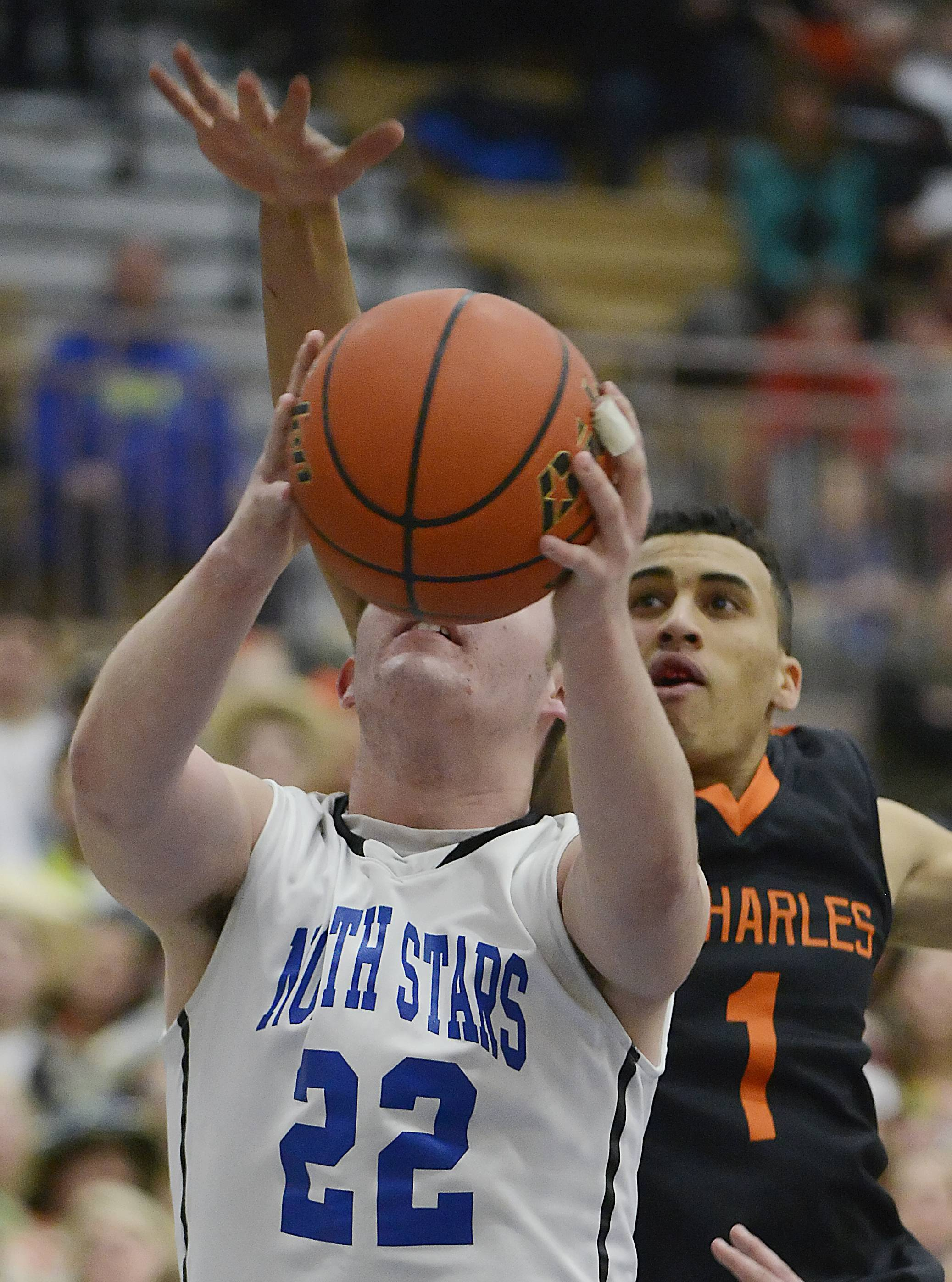 St. Charles North's Shane Dunteman tries to block a shot by St. Charles East's James McQuillan Wednesday in the regional game at St. Charles North.
