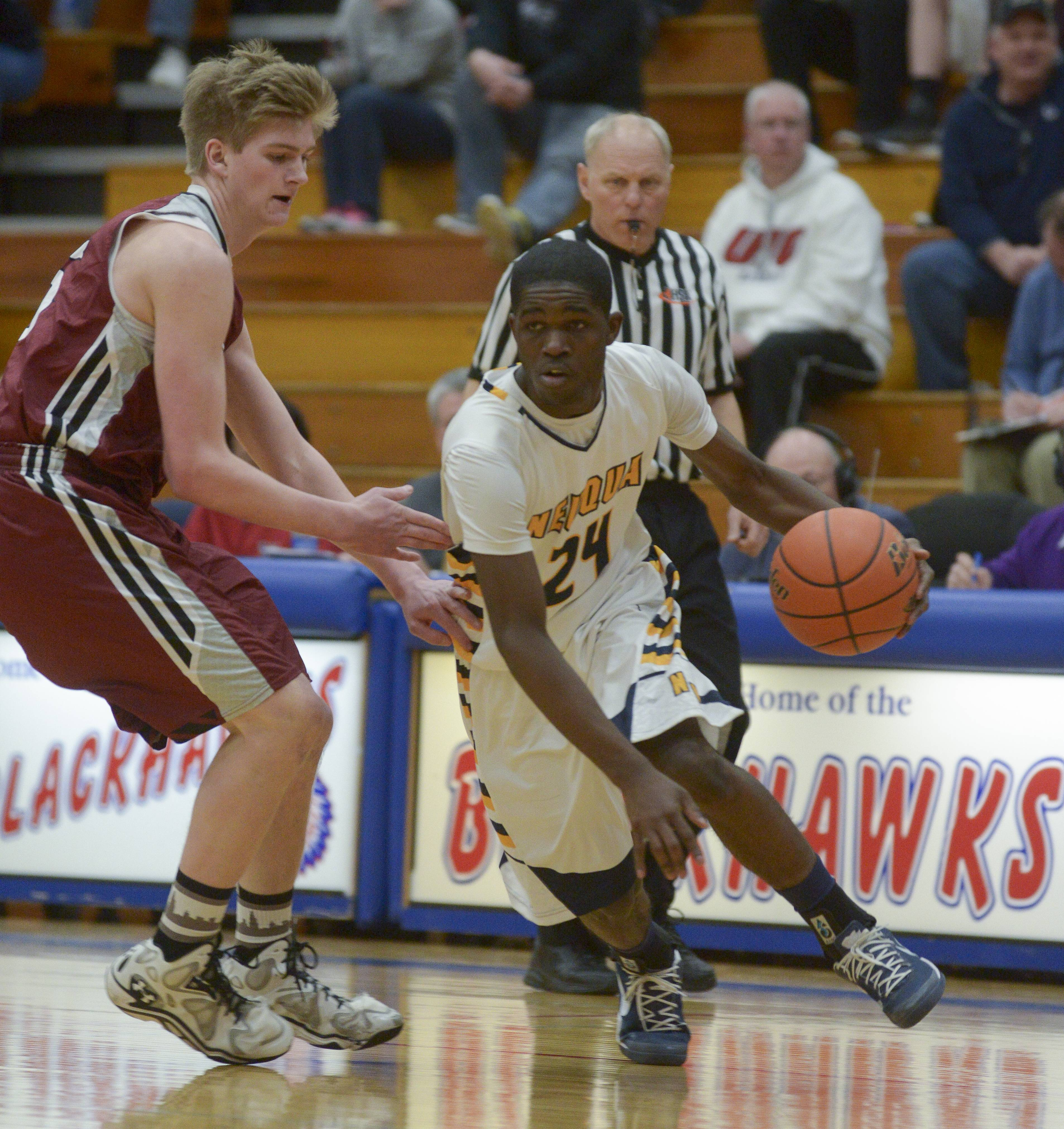 Neuqua Valley's Demond George drives around Plainfield North's Trevor Stumpe .