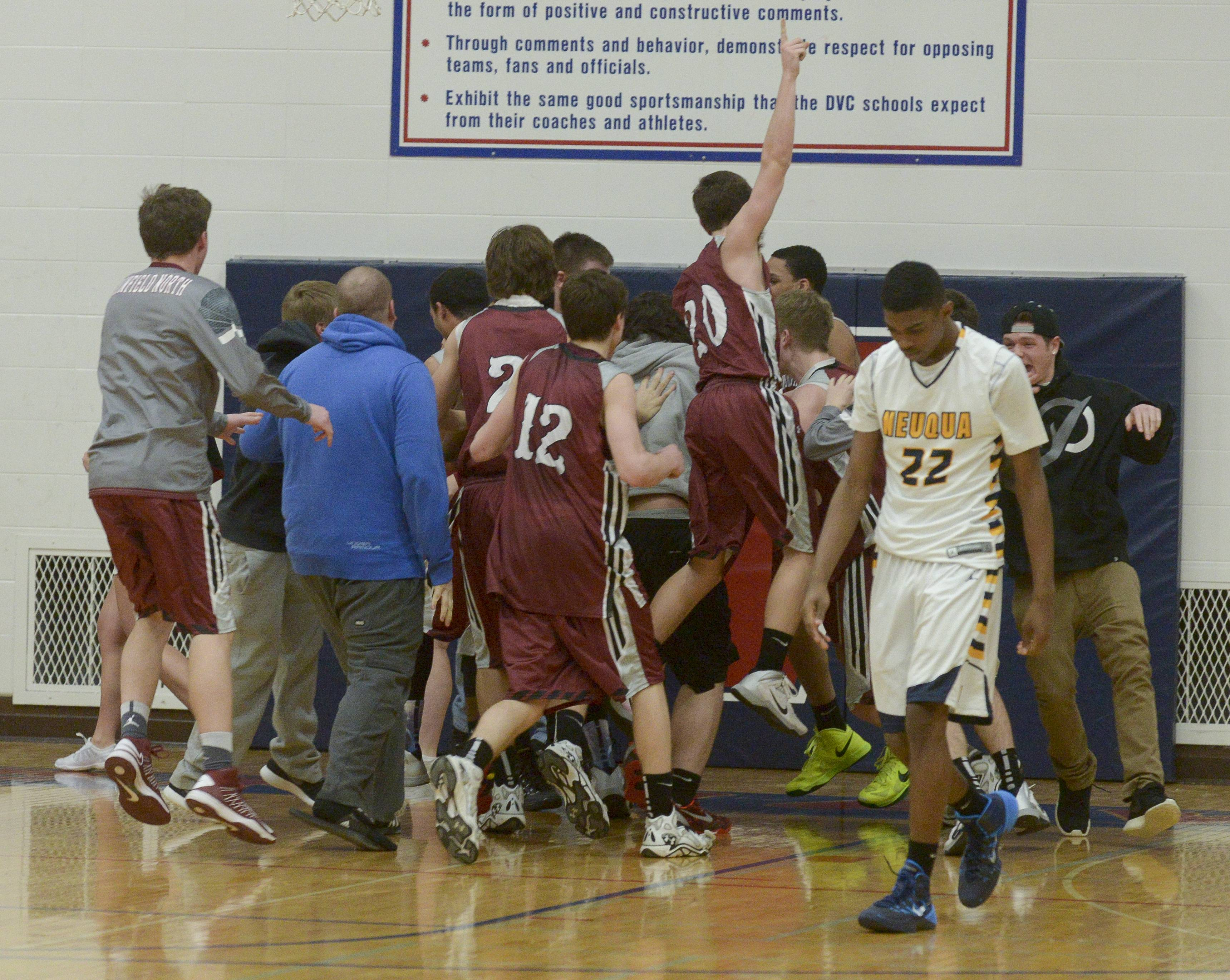 Neuqua Valley's Elijah Robertson walks off the court as  Plainfield North players celebrate.