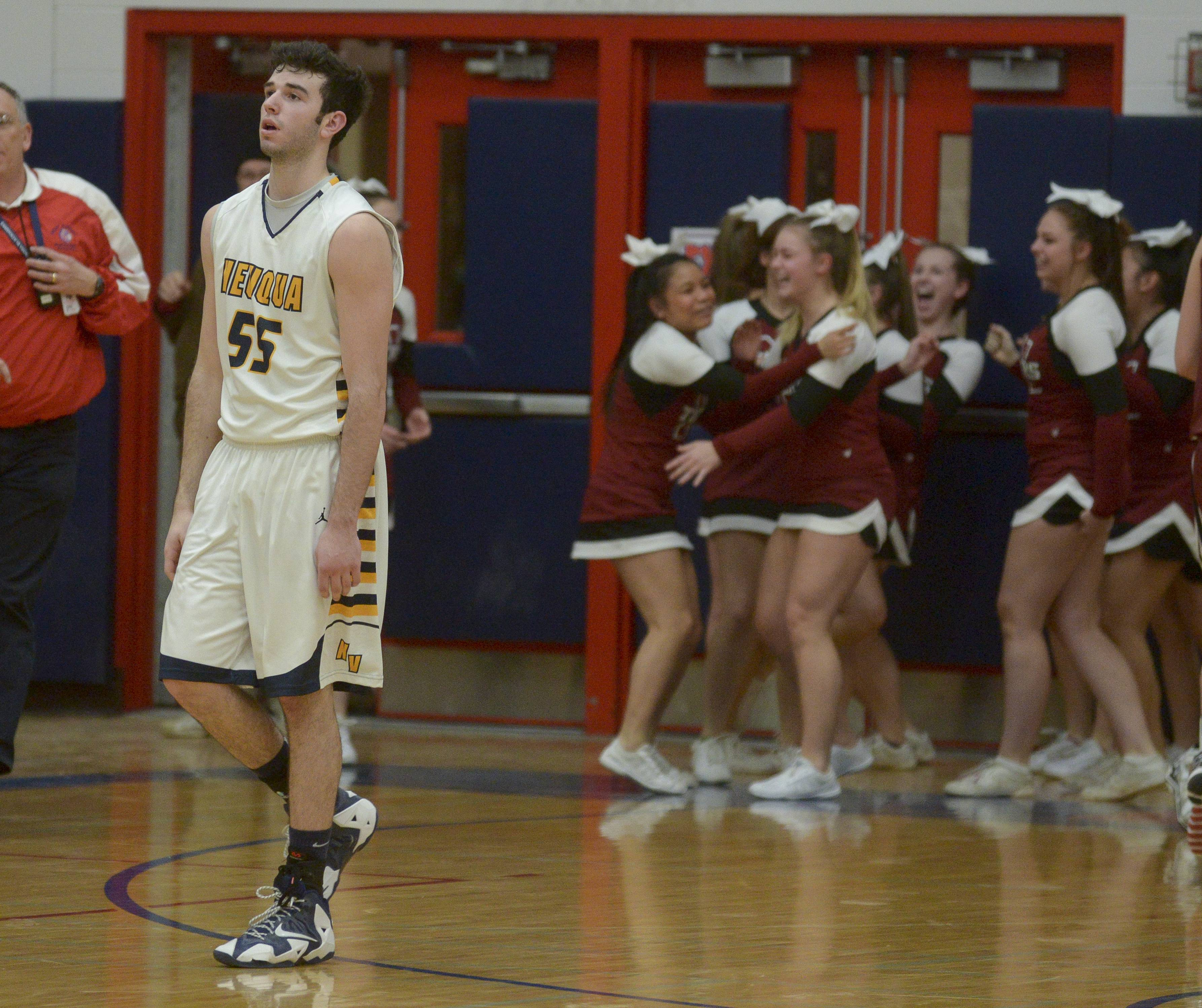 Neuqua Valley's Zach Incaudo walks off the court as  Plainfield North players celebrate.