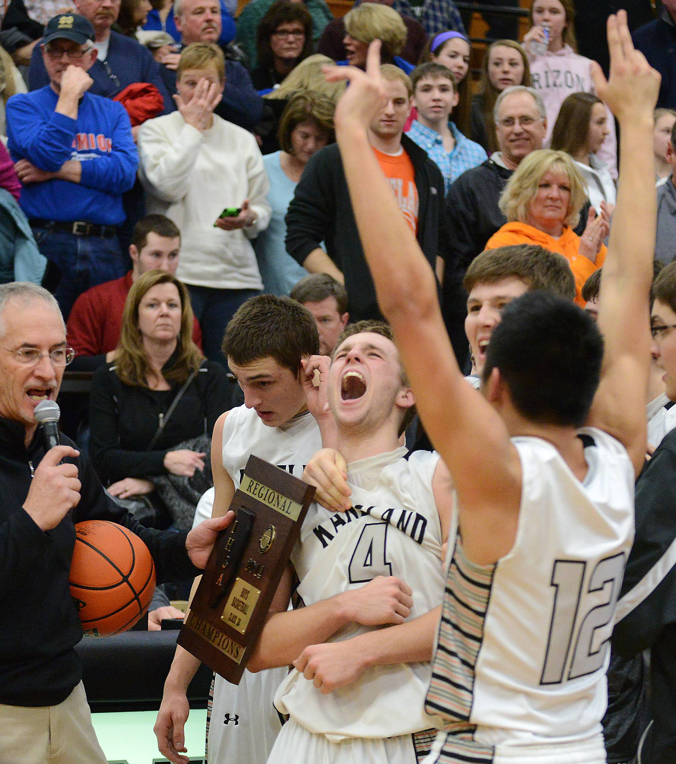 Kaneland players including Drew David (4) and Ben Barnes (12) celebrate as they're awarded the championship plaque after winning Friday's regional title game in Maple Park.