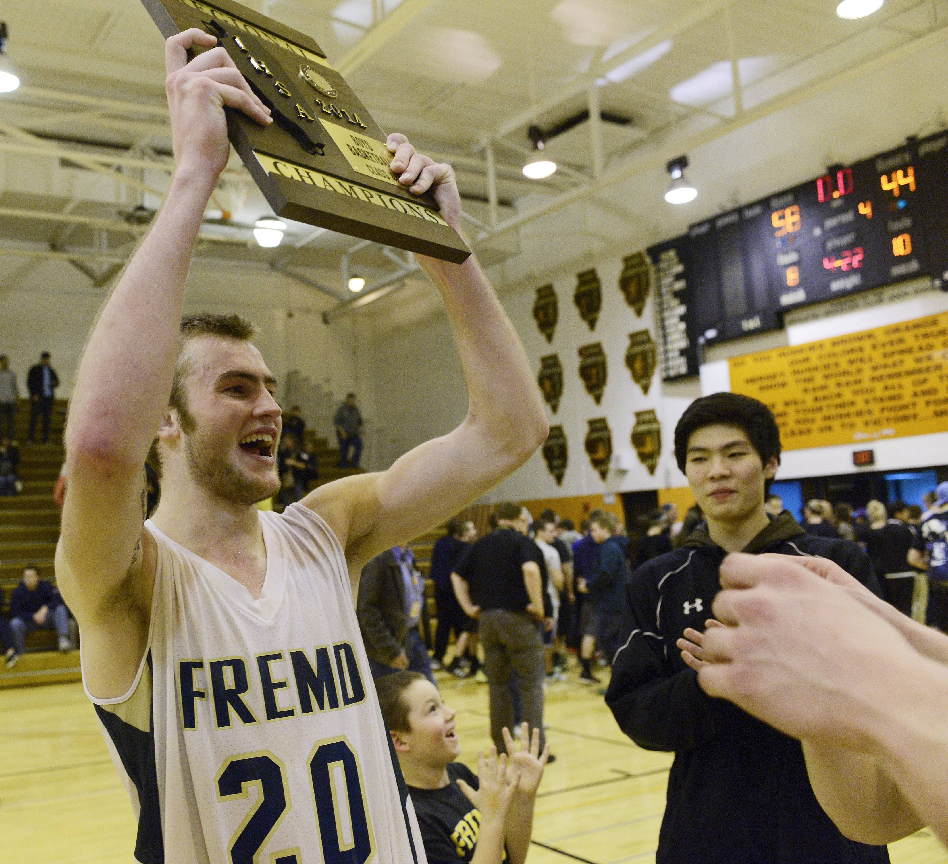 Fremd's Riley Glassmann holds up the championship plaque following Friday's 58-44 victory over Lake Zurich in the regional championship game at Hersey High School in Arlington Heights.