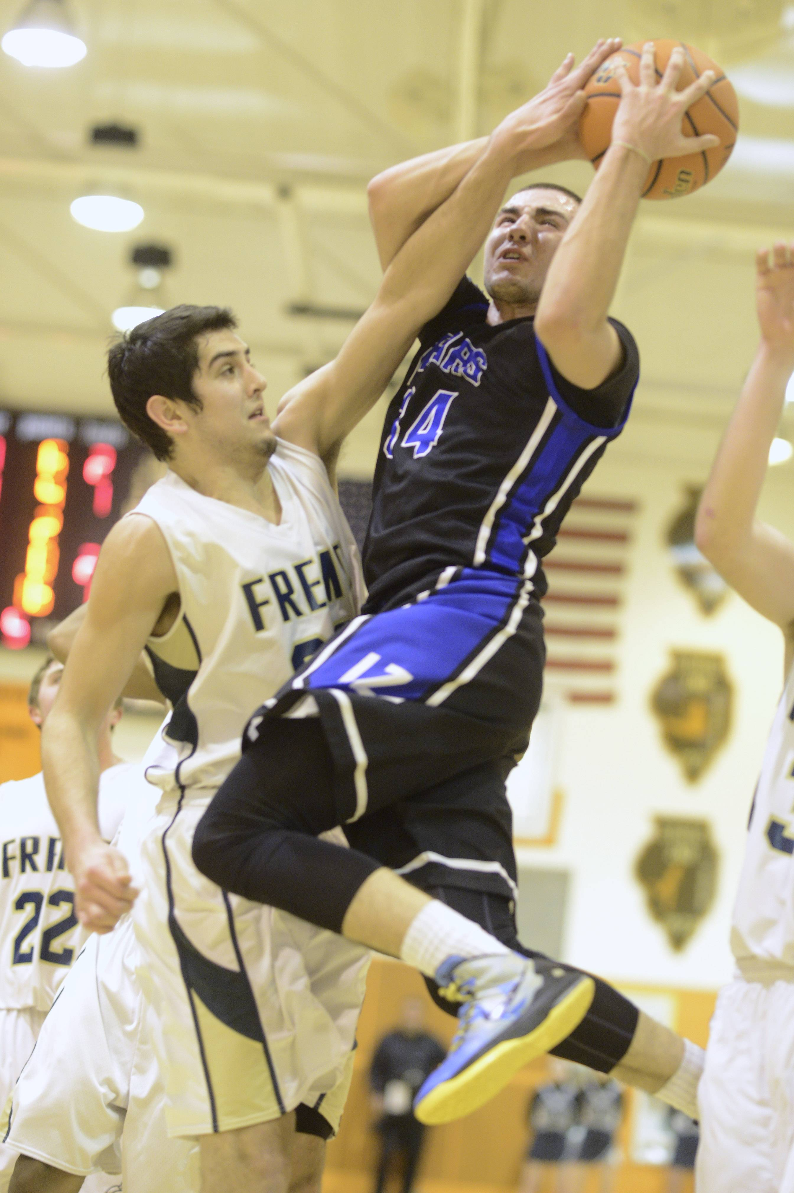 Lake Zurich's Mike Travlos, right, goes strong to the basket against Fremd's Matthew Ochoa.