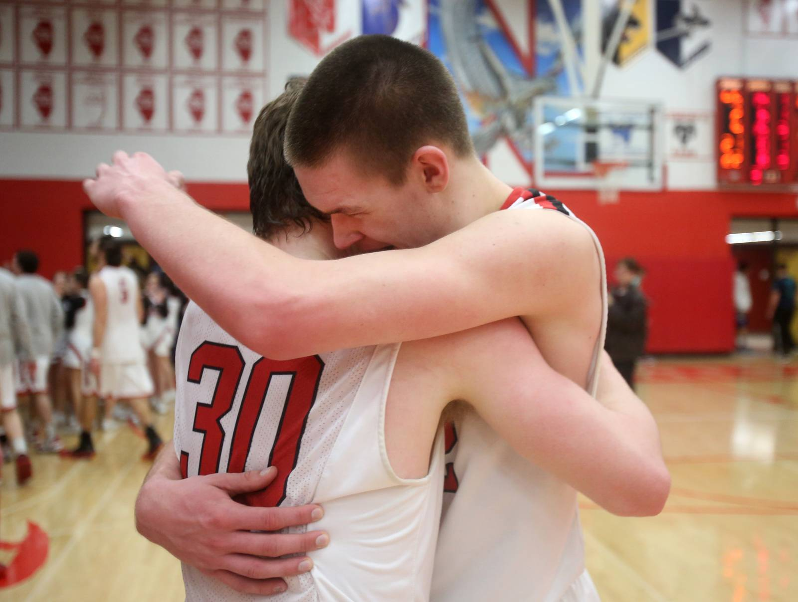 Hinsdale Central's Chase Hamilton, left, gets a hug from Matt Rafferty, right, as both celebrate Hamilton's game-winning shot.