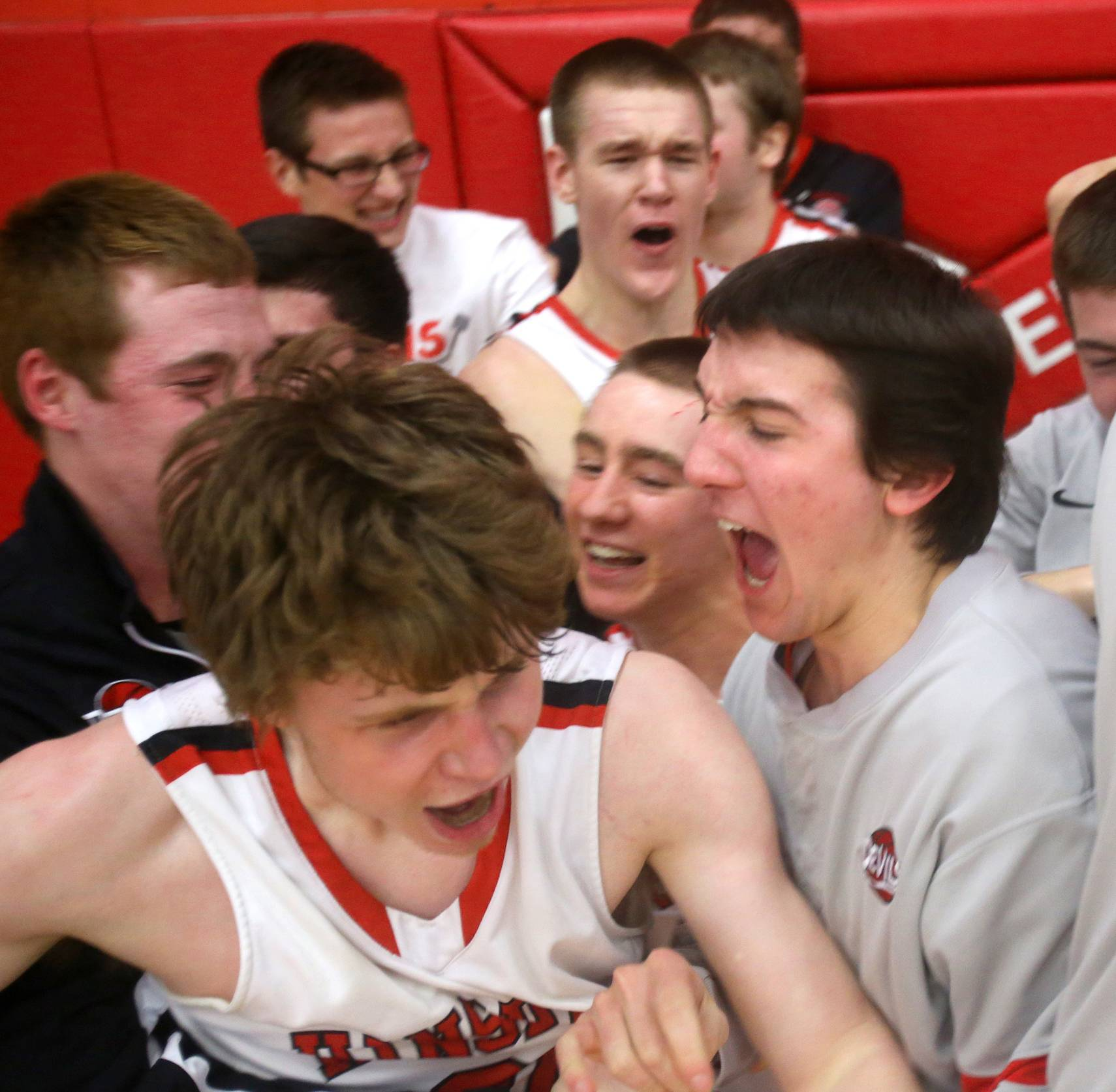 Hinsdale Central's Chase Hamilton is mobbed by teammates after sinking a buzzer shot.
