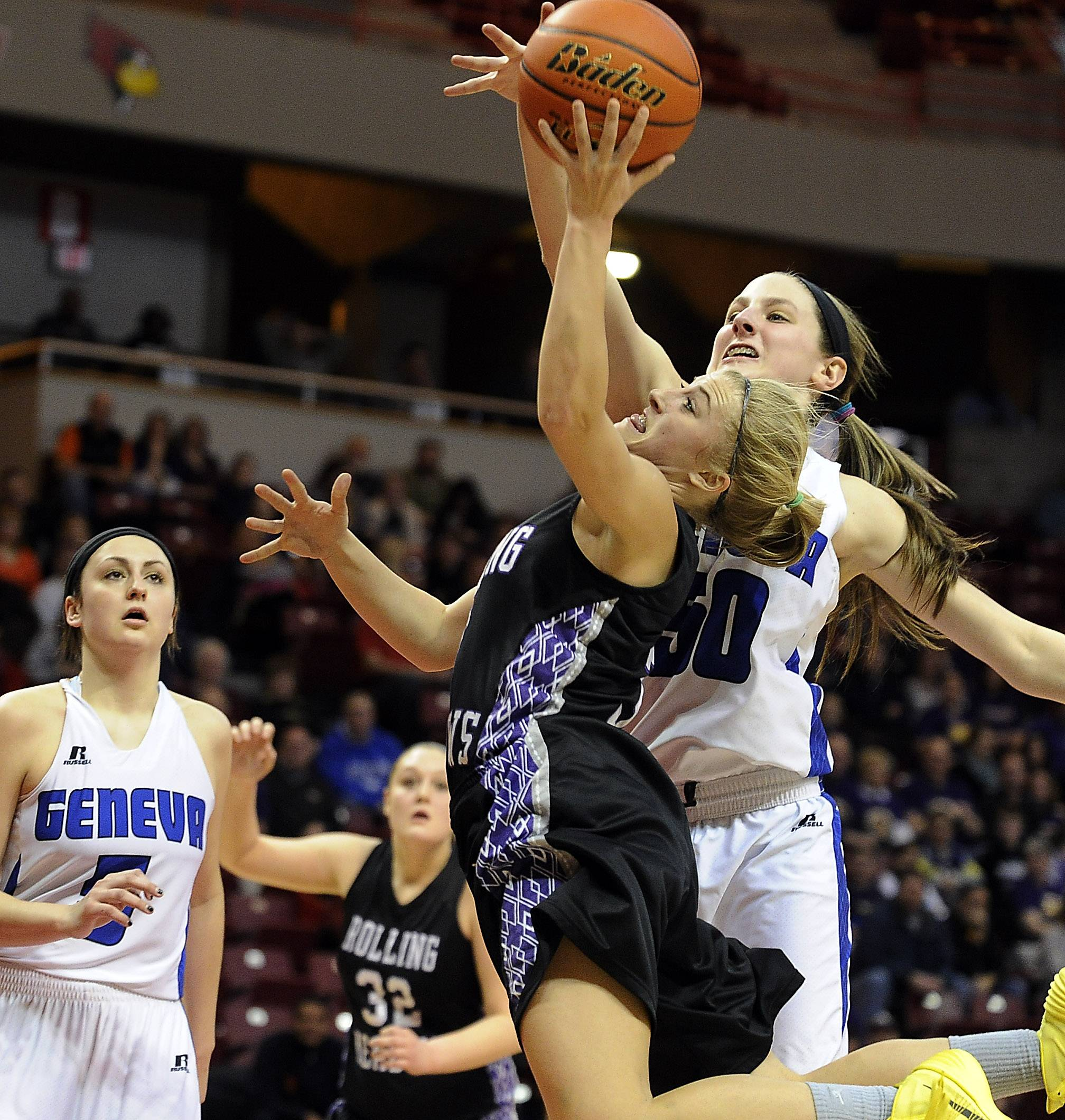 Rolling Meadows' Jackie Kemph delivers to the basket but is blocked by Geneva's Grace Loberg.