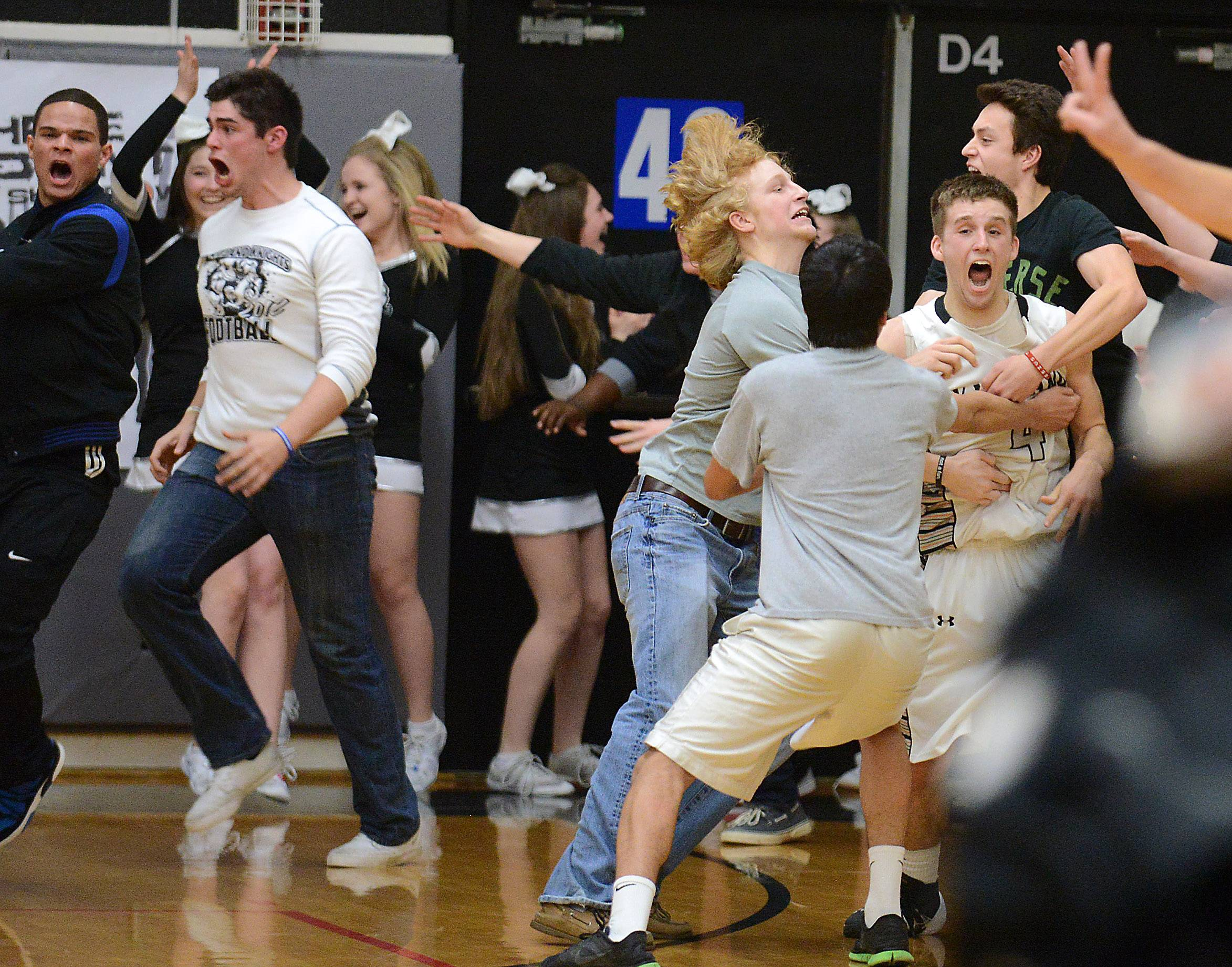 Kaneland's Drew David, right, is swarmed by fans after hitting a last-second game-winning shot .