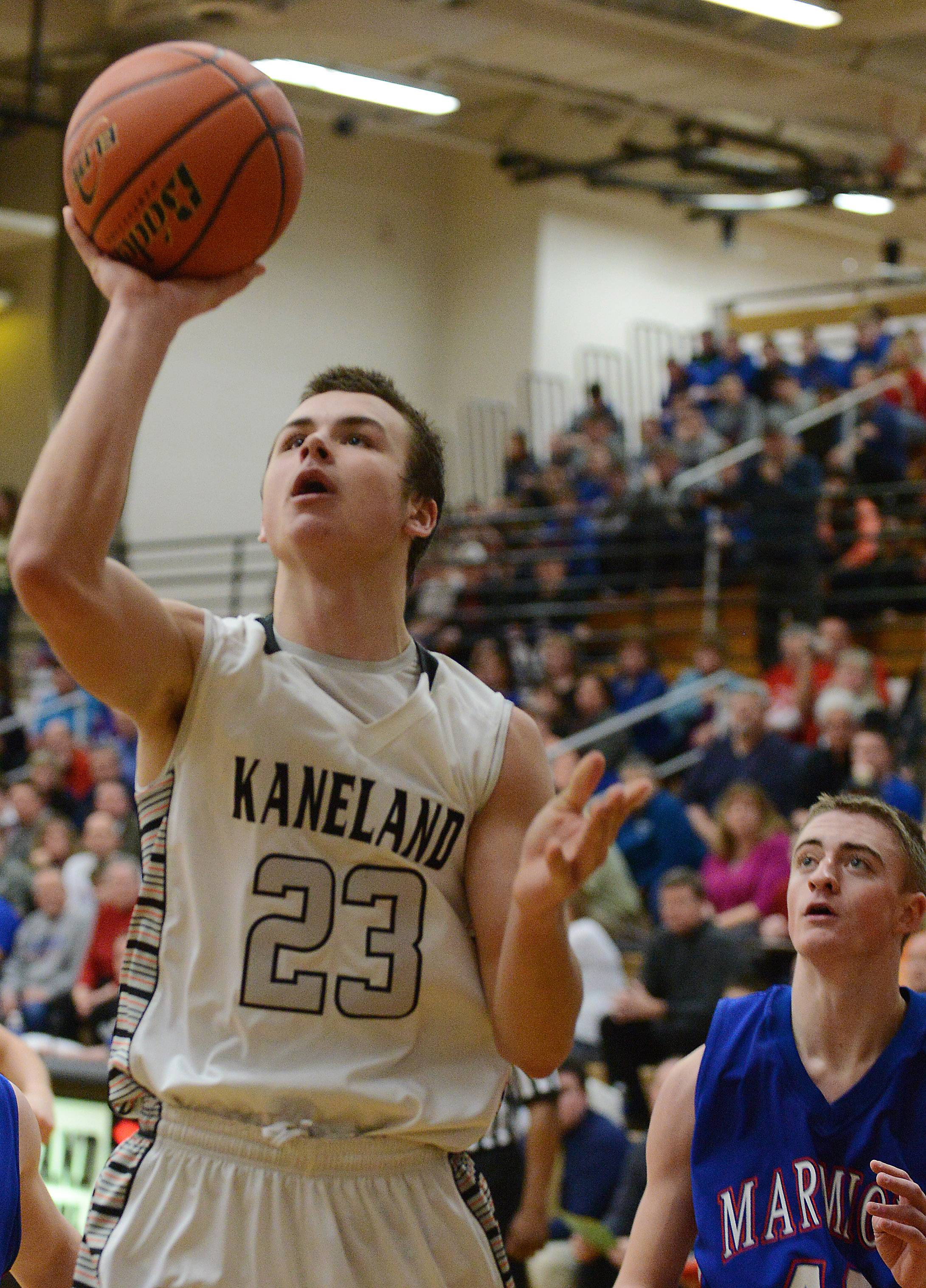 Kaneland's Tyler Carlson slips into the lane and scores on a running one-hander.
