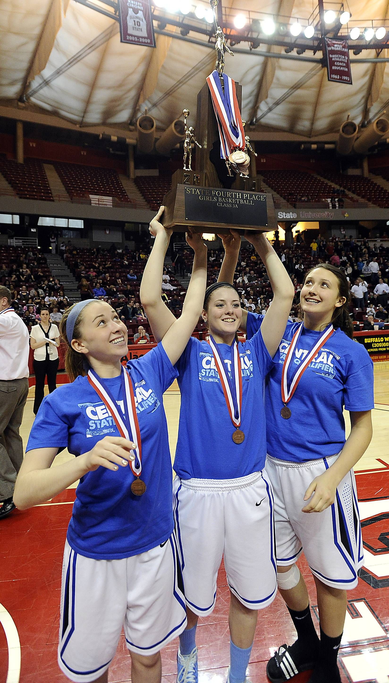 Burlington Central's Kathleen Ratzek, Kayla Ross and Alison Colby hoist the Class 3A fourth-place state trophy at Redbird Arena on Saturday.