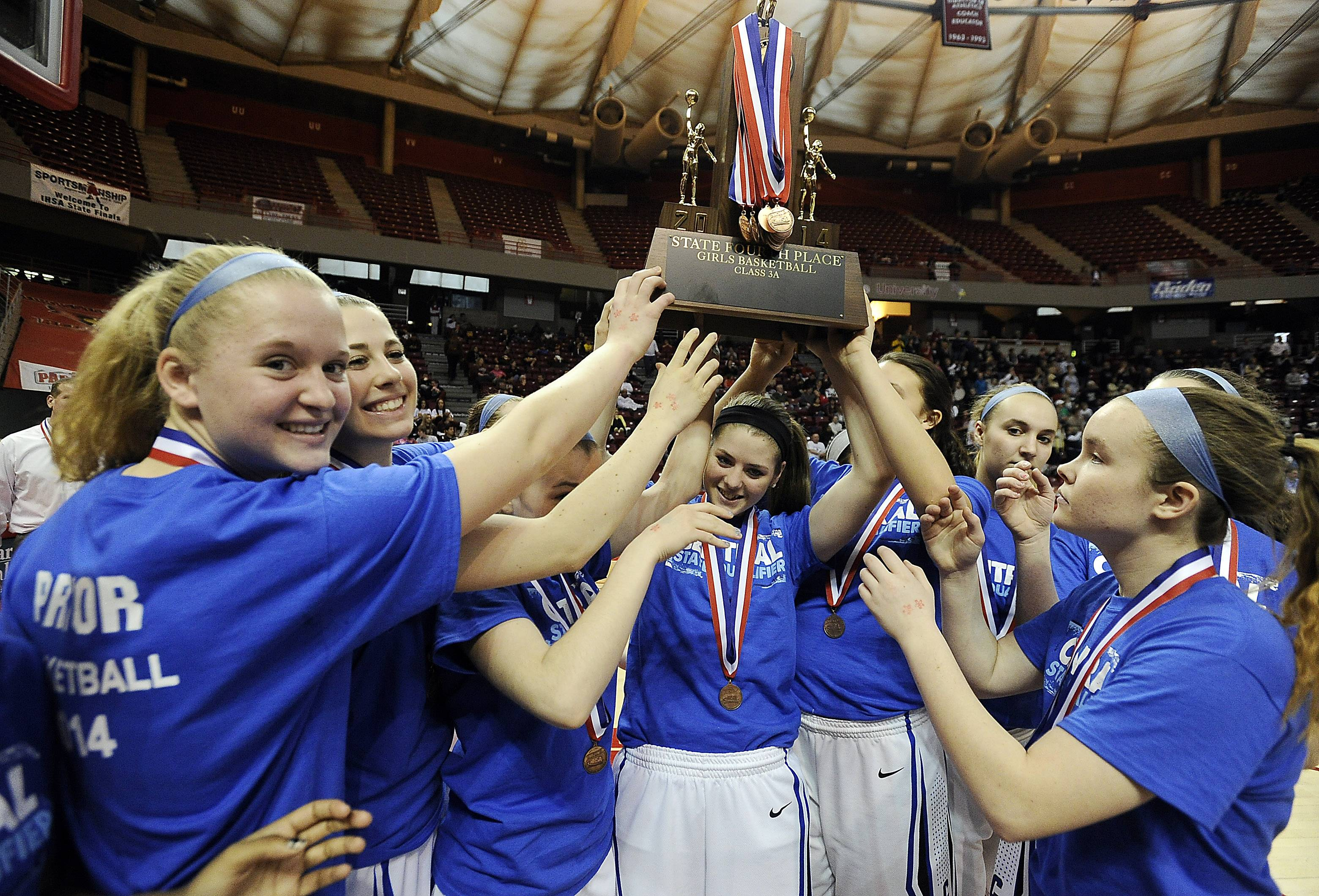 Burlington Central's girls basketball team hoists the Class 3A fourth-place trophy Saturday at Redbird Arena in Normal.