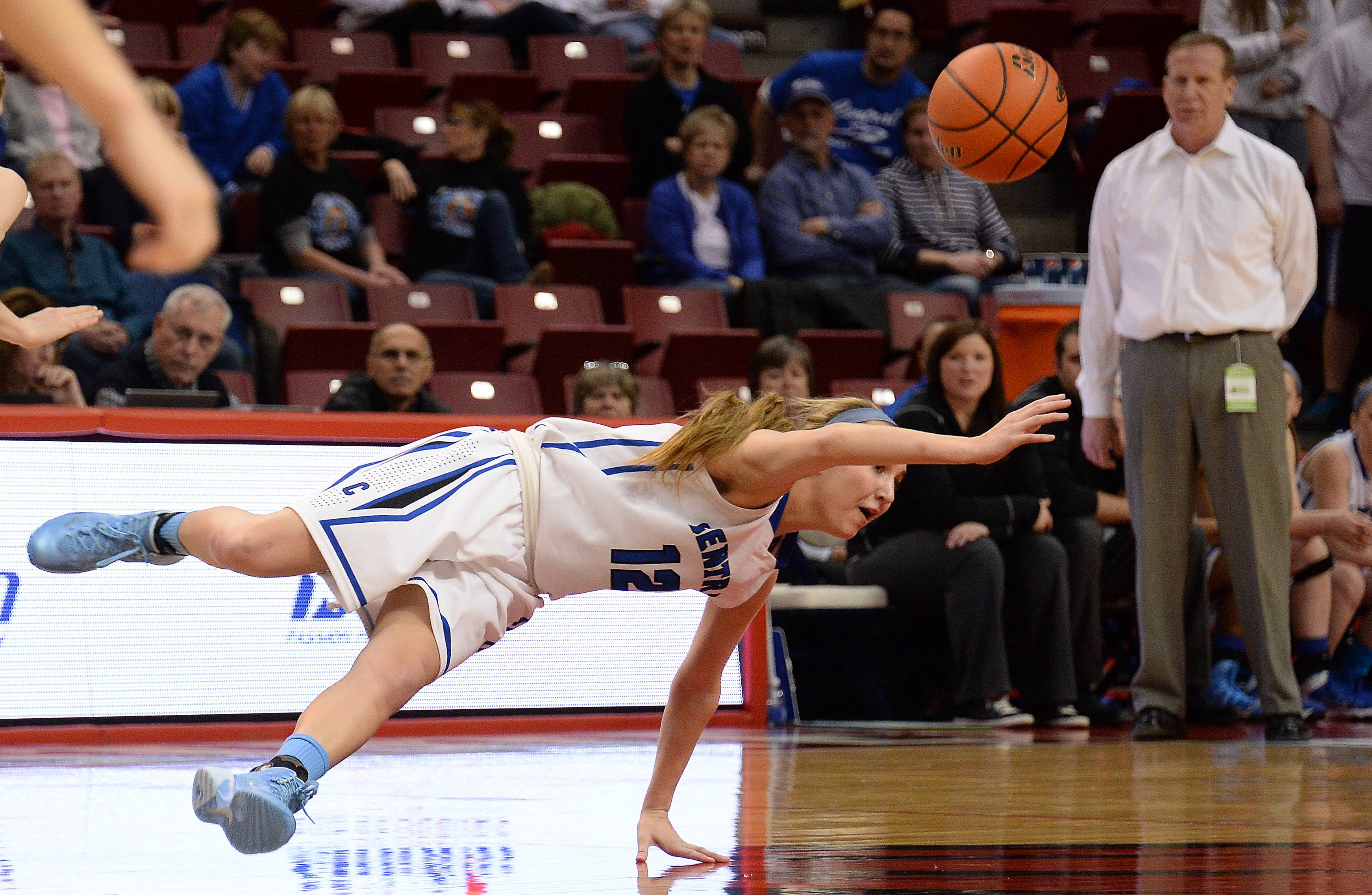 Burlington Central's Shelby Holt is tripped up as she scrambles for a loose ball in the first period of girls state basketball in the third place game in Normal on Saturday.