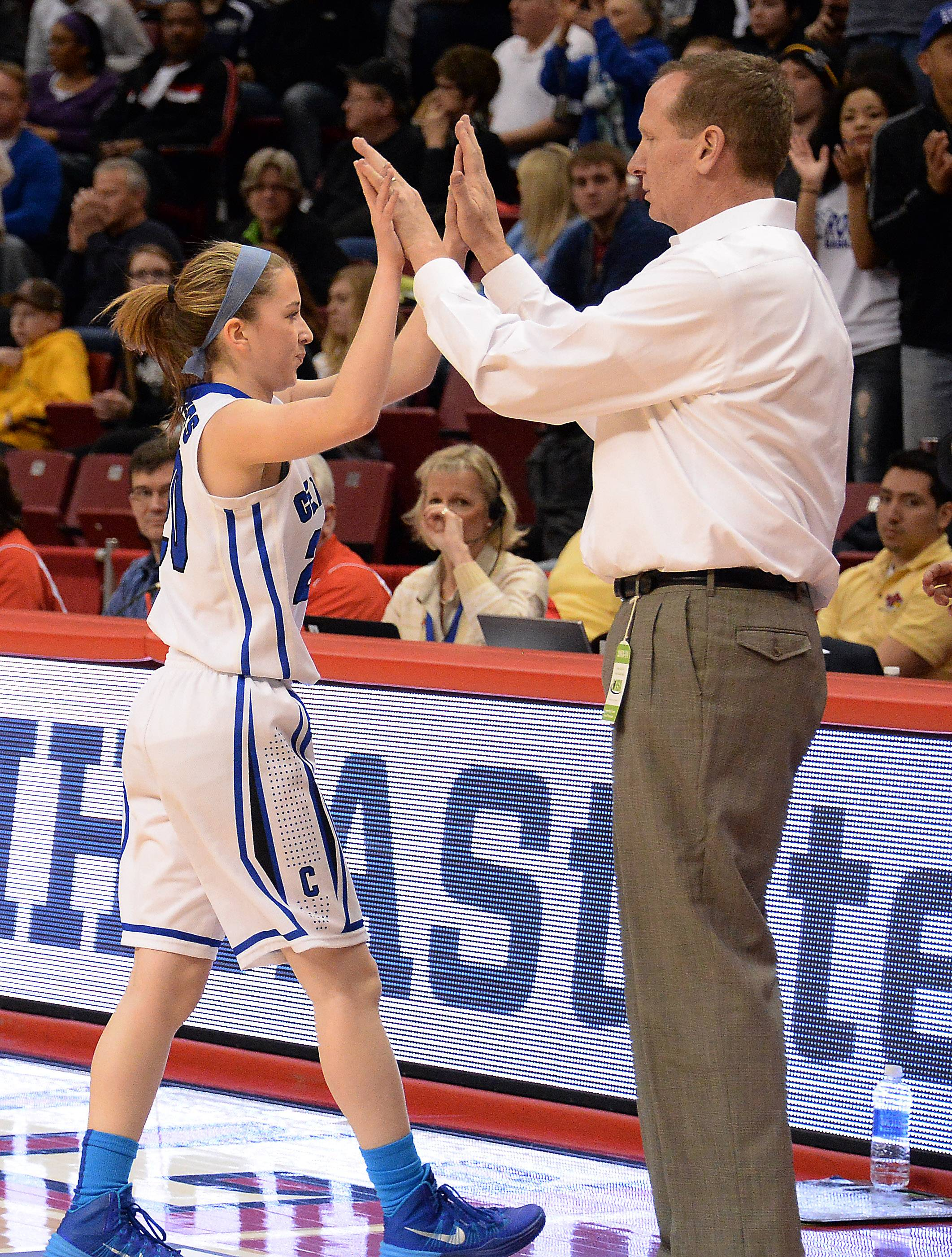 Burlington Central's Kathleen Ratzek, the only senior on the team,  high-fives her coach ,Mark Smith, as she exits the floor at the end of the game Saturday in Normal.i