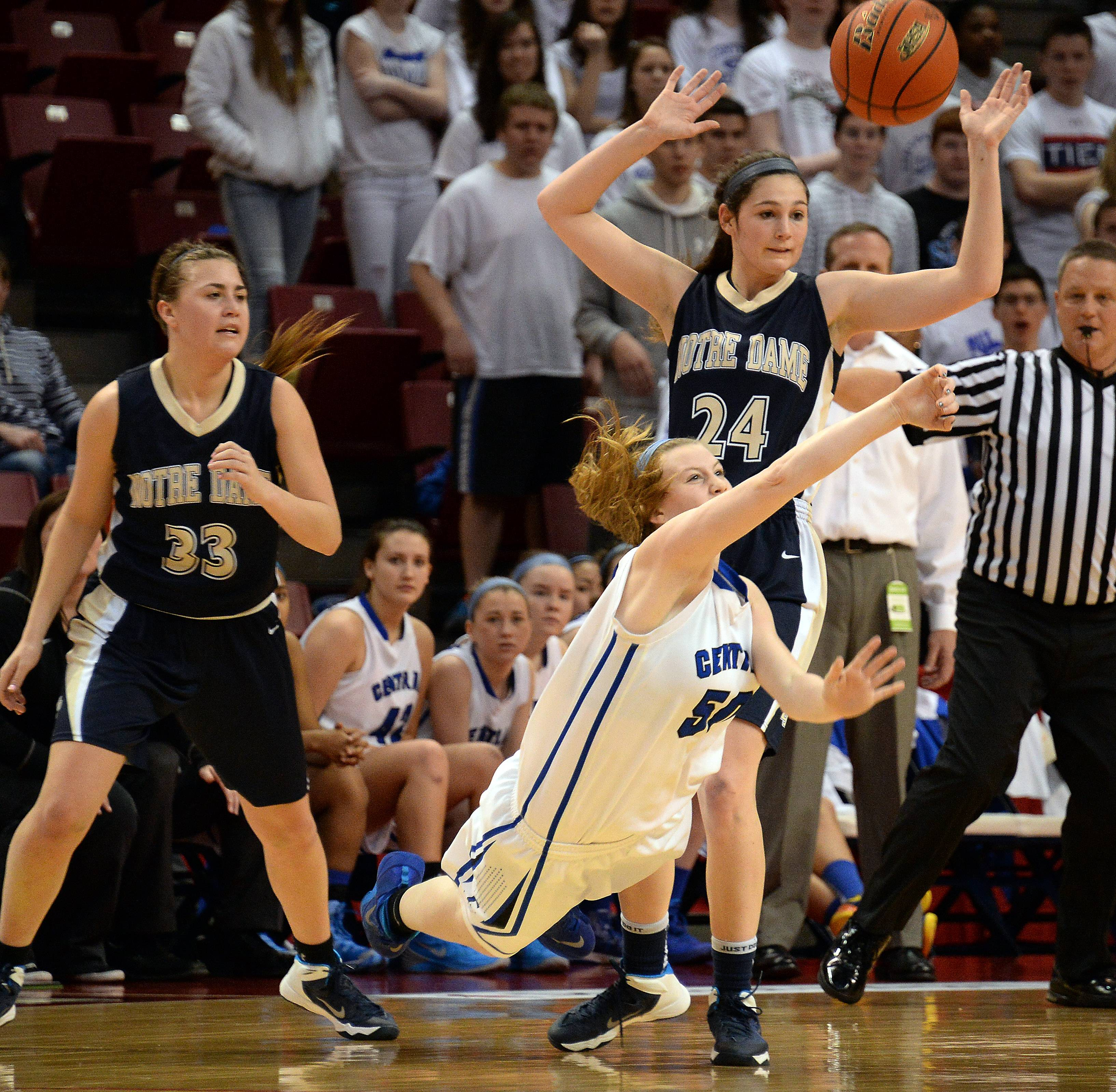 Burlington Central's Becca Gerke passes the ball as she gets tripped up by Quincy Notre Dame's Mary Beth Hugenberg in the first period of girls state basketball in the third place game in Normal on Saturday.