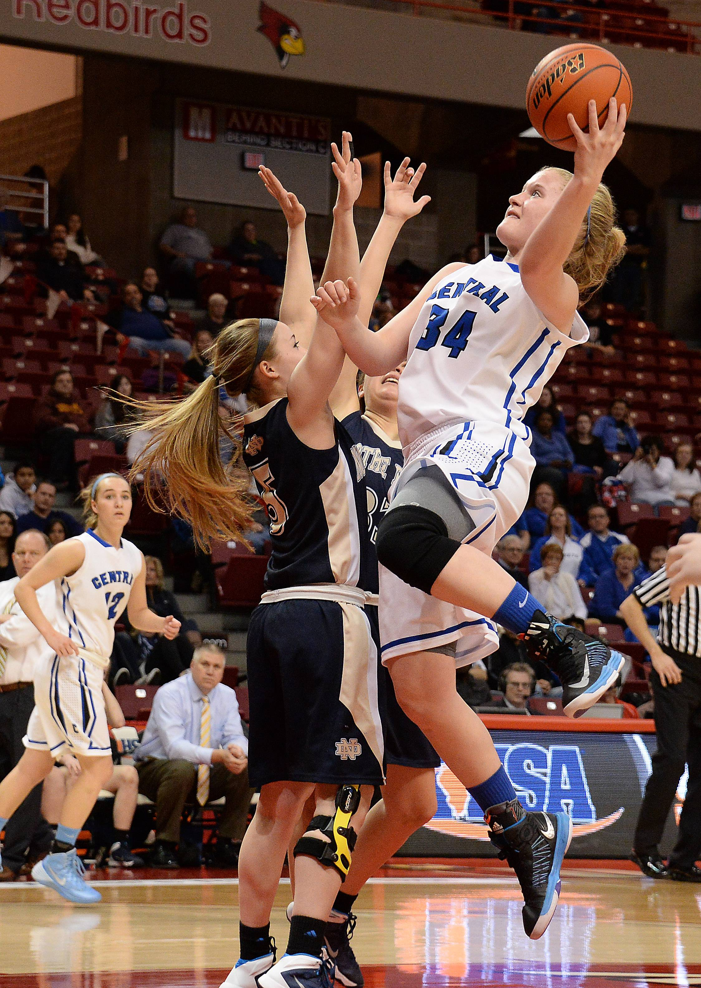 Burlington Central's Sam Pryor goes for the shot as Quincy Notre Dame's defense applies pressure in the first period of girls state basketball in the third place game in Normal on Saturday.