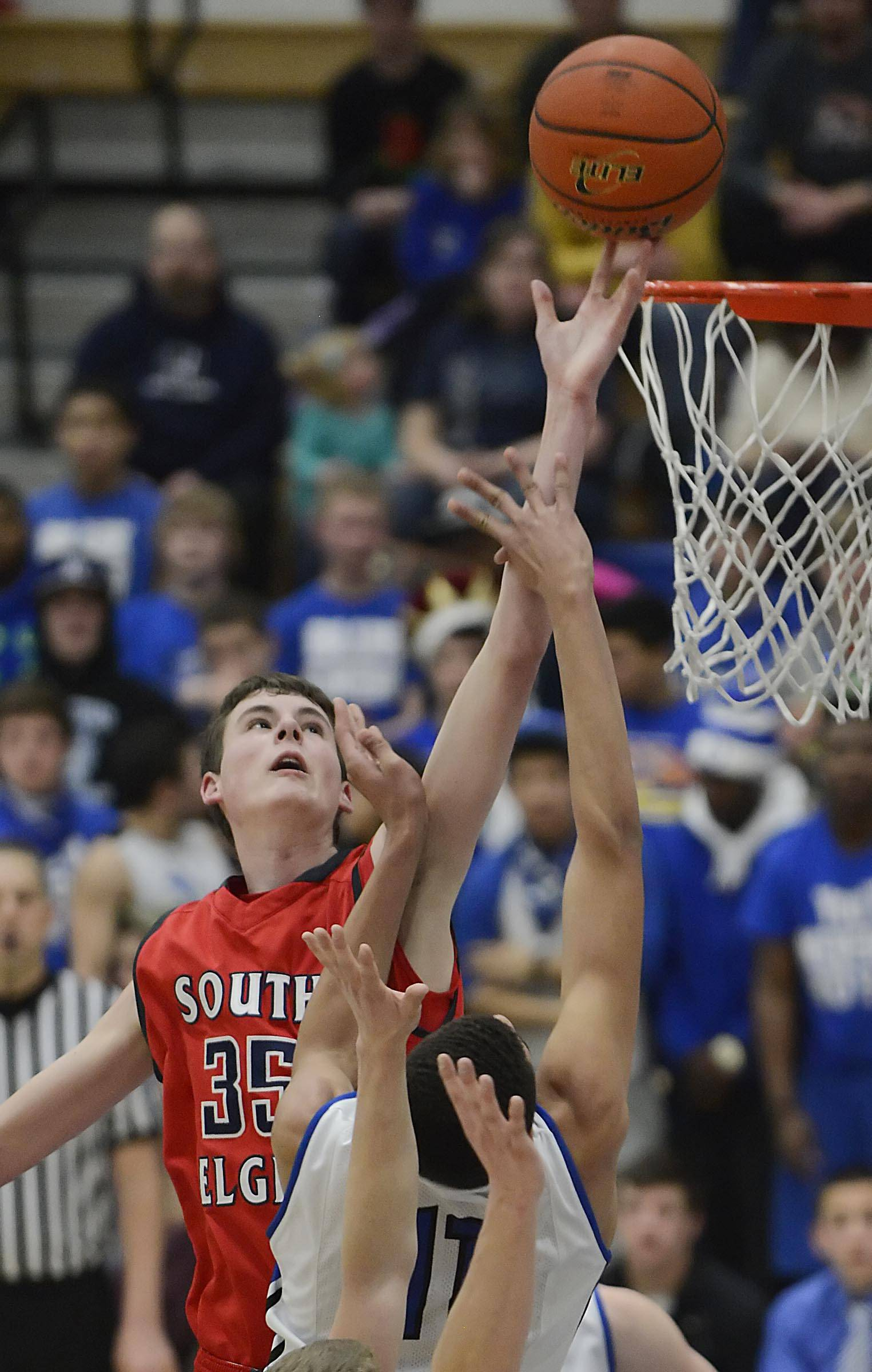John Starks/jstarks@dailyherald.com  South Elgin's Tyler Hankins stretches for a rebound over Larkin's Christian Negron Tuesday in the St. Charles North regional game.