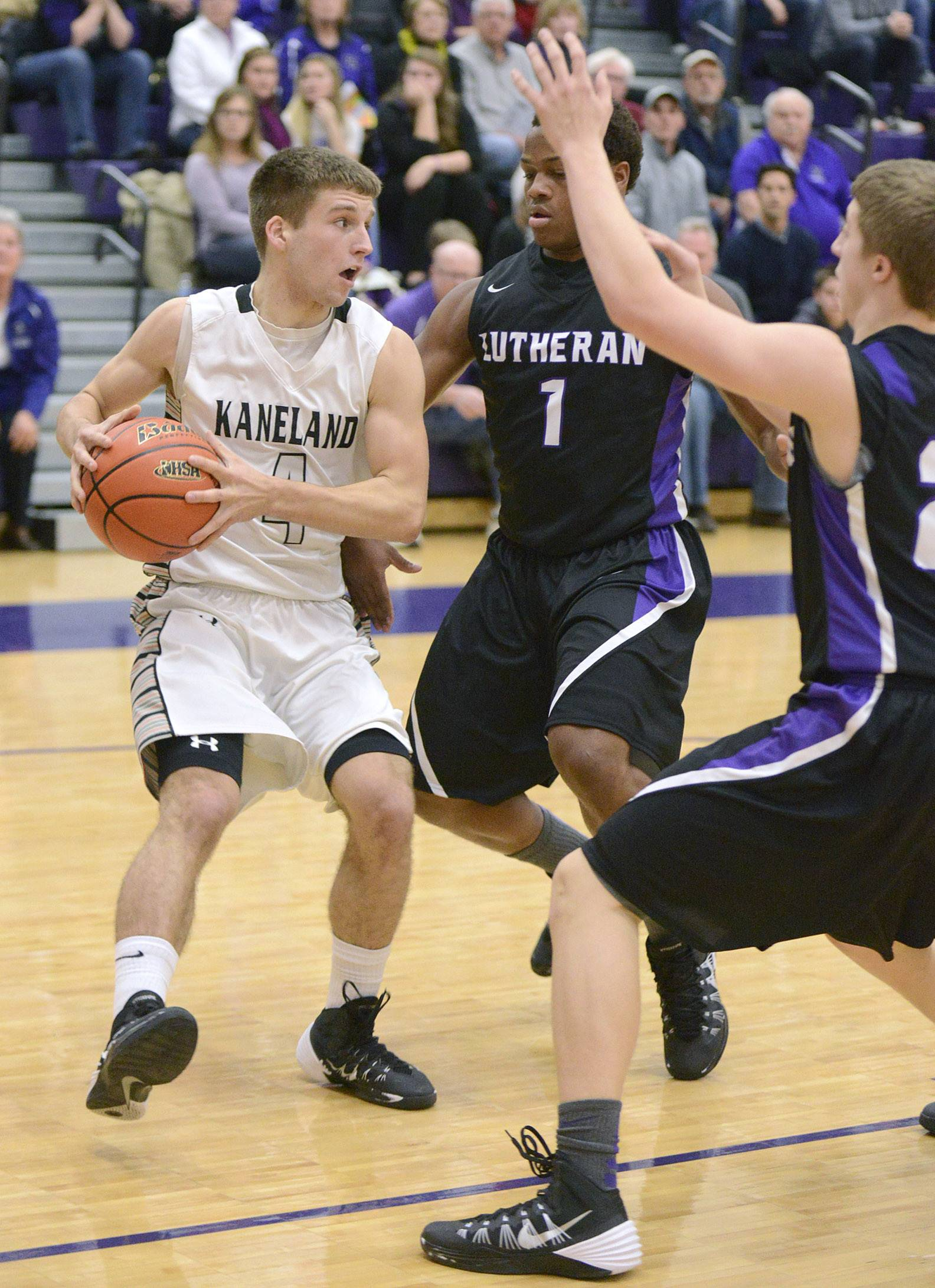Kaneland's Drew David looks to pass around a block by Rockford Lutheran's James Robinson (1) and Joseph Kellen in the first quarter of the Class 3A sectional game at Hampshire HIgh School on Tuesday, March 11.