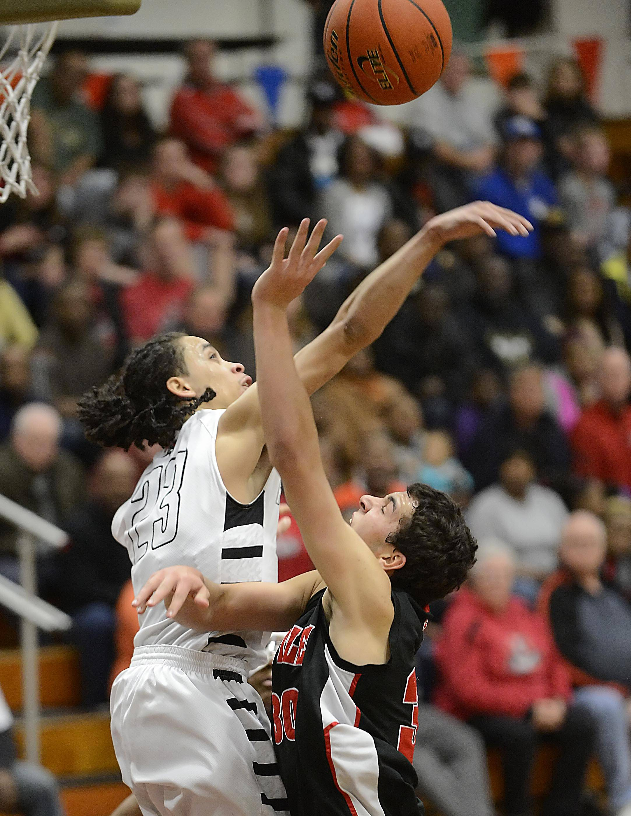 Huntley's Riley Wicks has his shot blocked by Rockford Auburn's Laytwan Porter in the Class 4A Elgin sectional semifinal Tuesday.