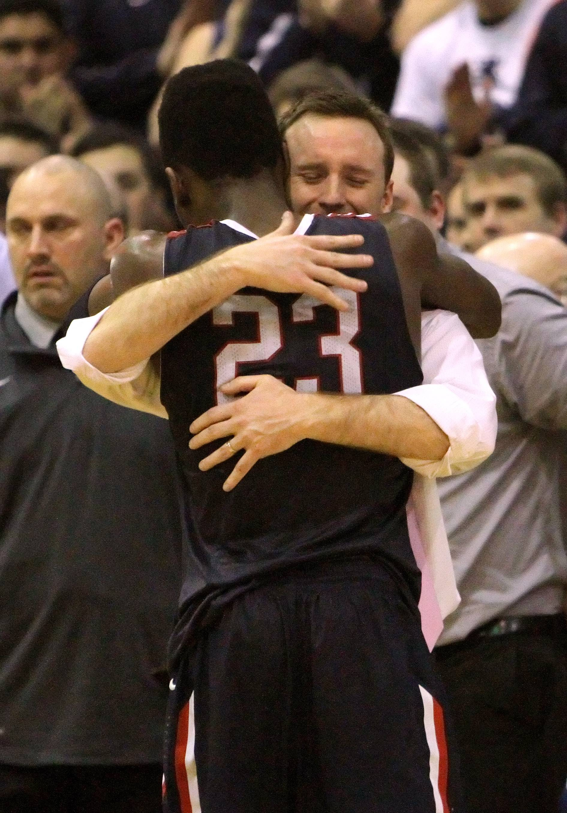 St. Viator coach Mike Howland hugs Ore Arogundade as he comes out of the game .