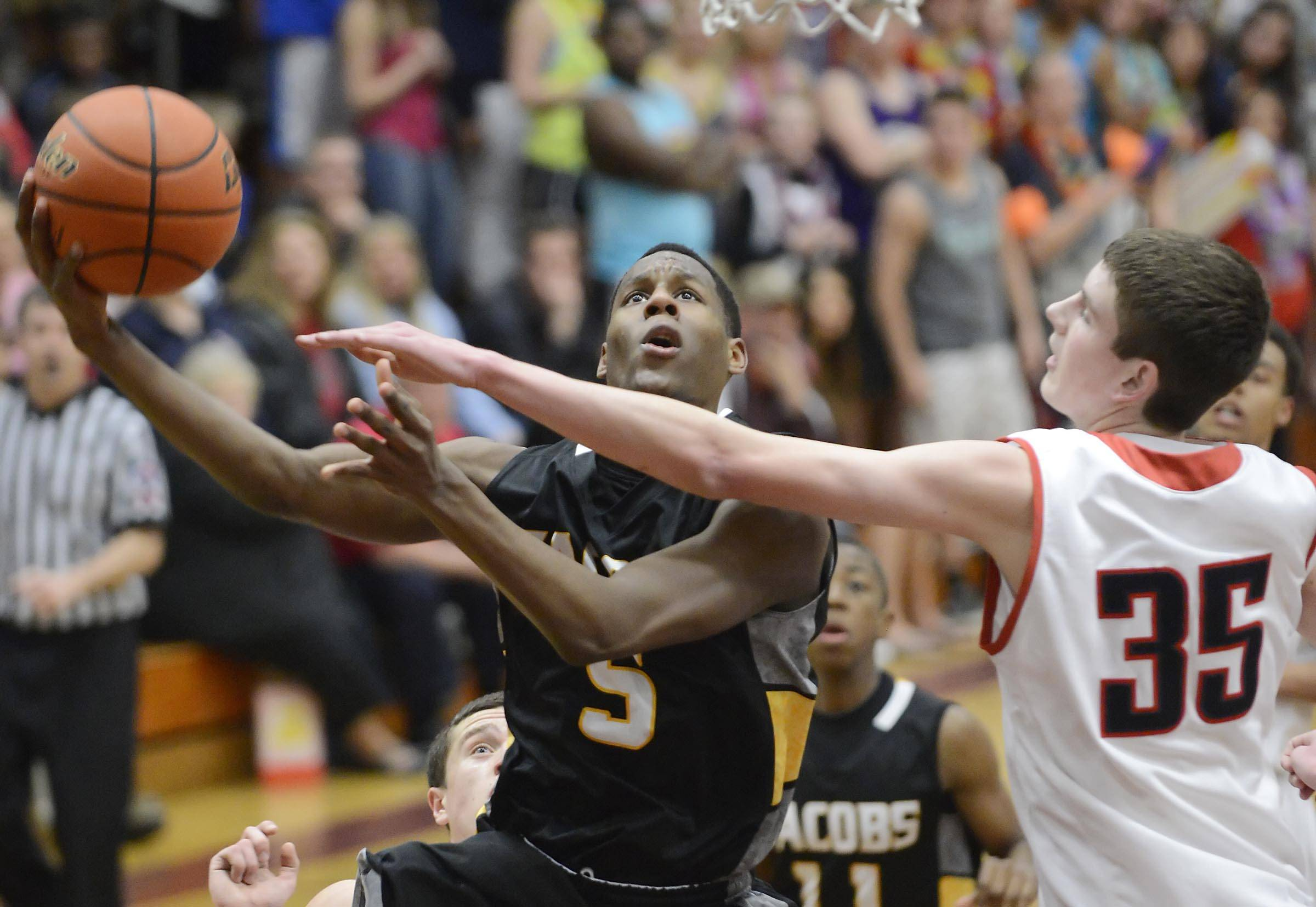 South Elgin's Tyler Hankins tries to block the shot of Jacobs' Chrishawn Orange Wednesday in the Class 4A Elgin sectional semifinal.