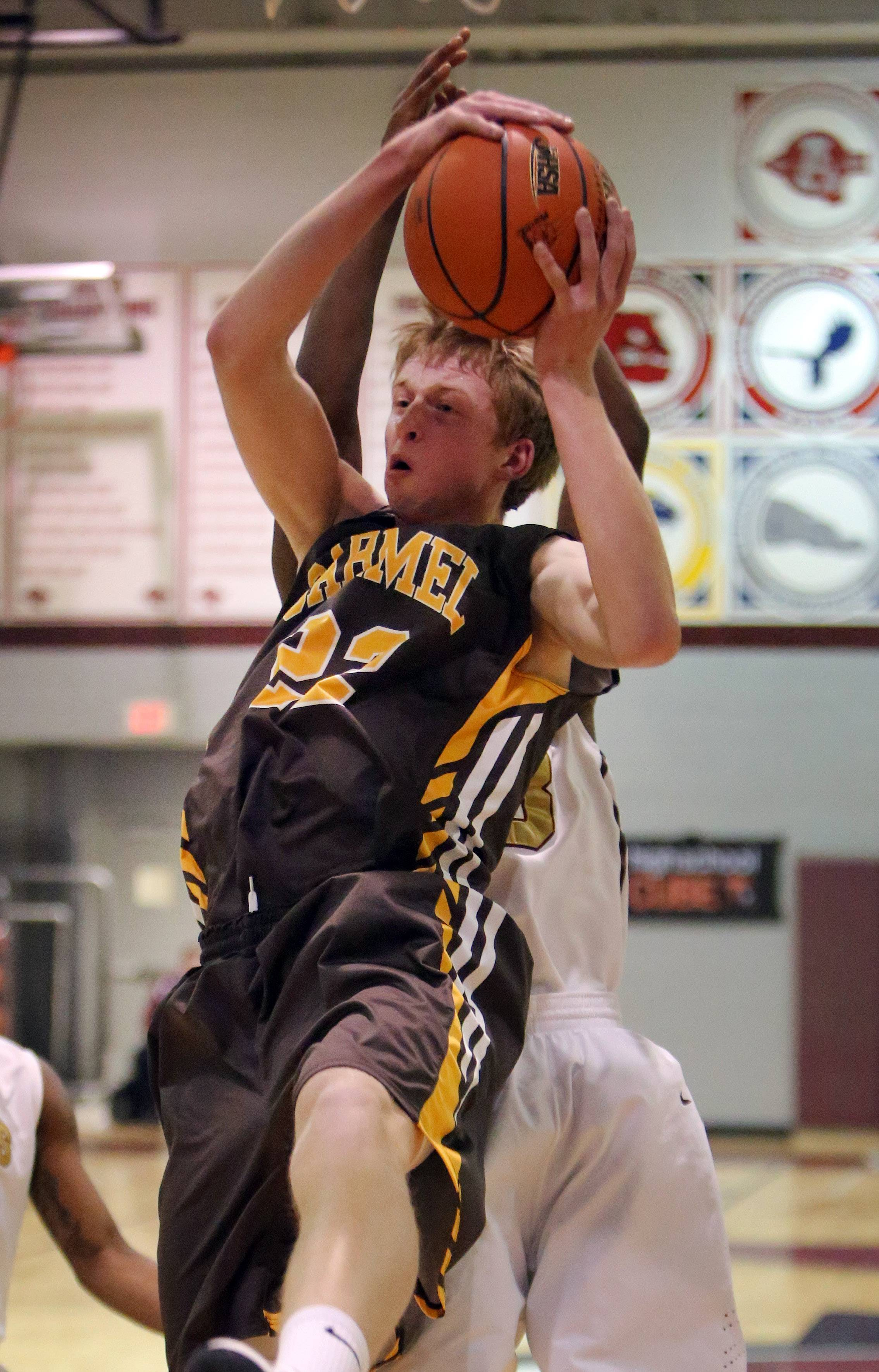 Carmel's Michael Barr pulls down a rebound during the Class 3A sectional semifinal at Antioch on Wednesday.