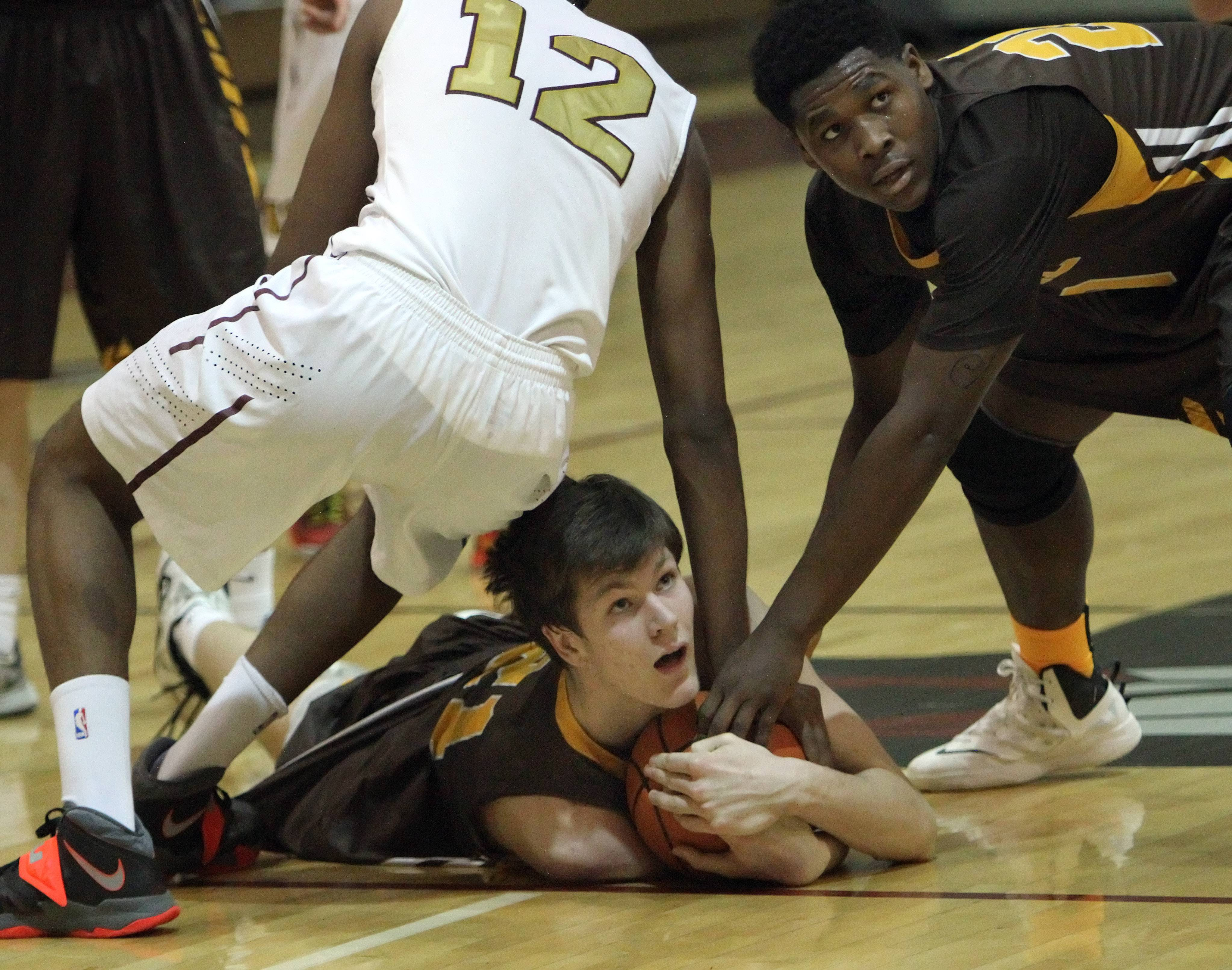 Carmel's Jack George, left, and Nickai Poyser try to secure a loose ball.