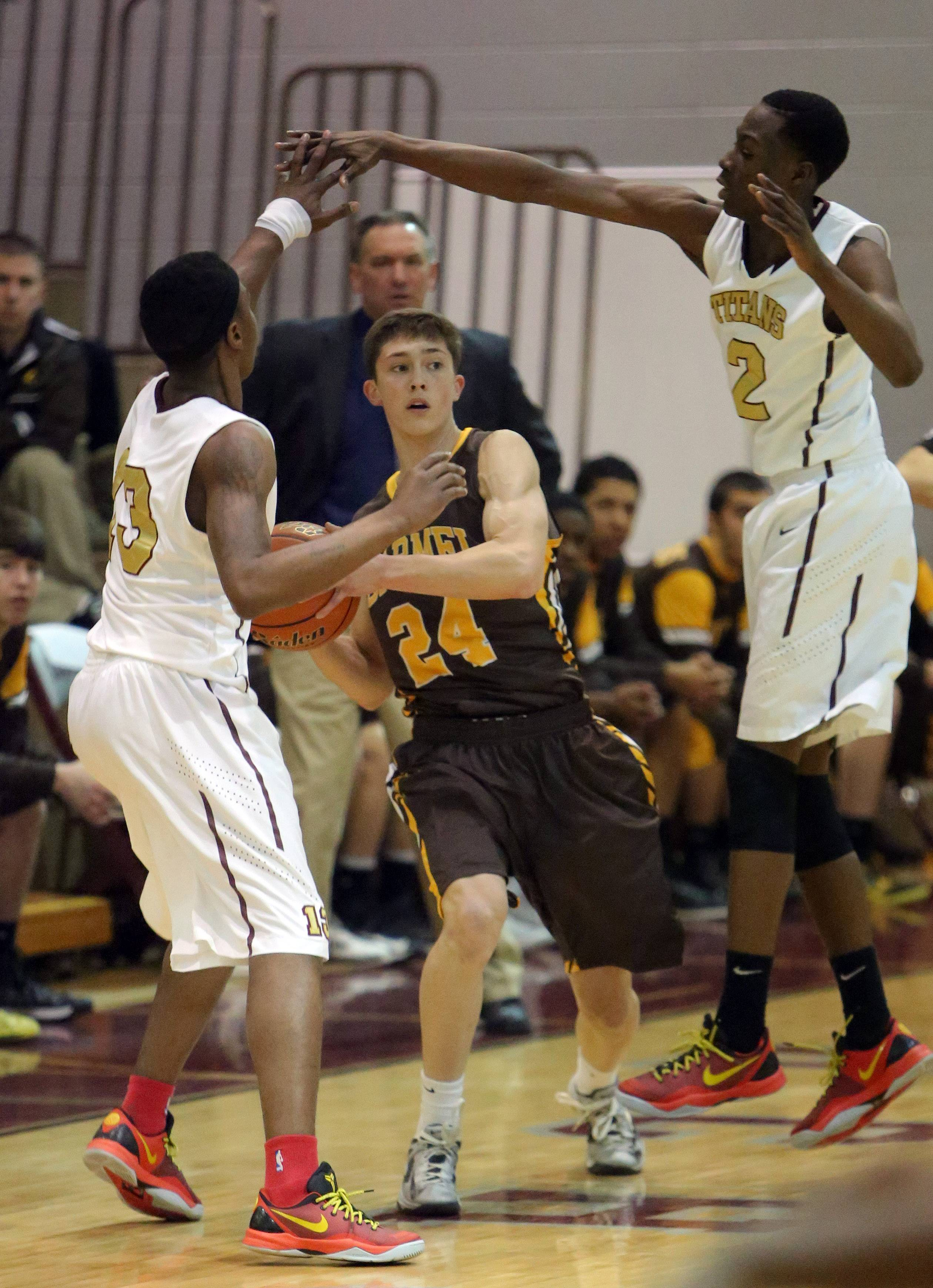 Carmel's Billy Kirby, middle, looks to pass as Uplift's Robert Gordon and Daniel Suetan defend.