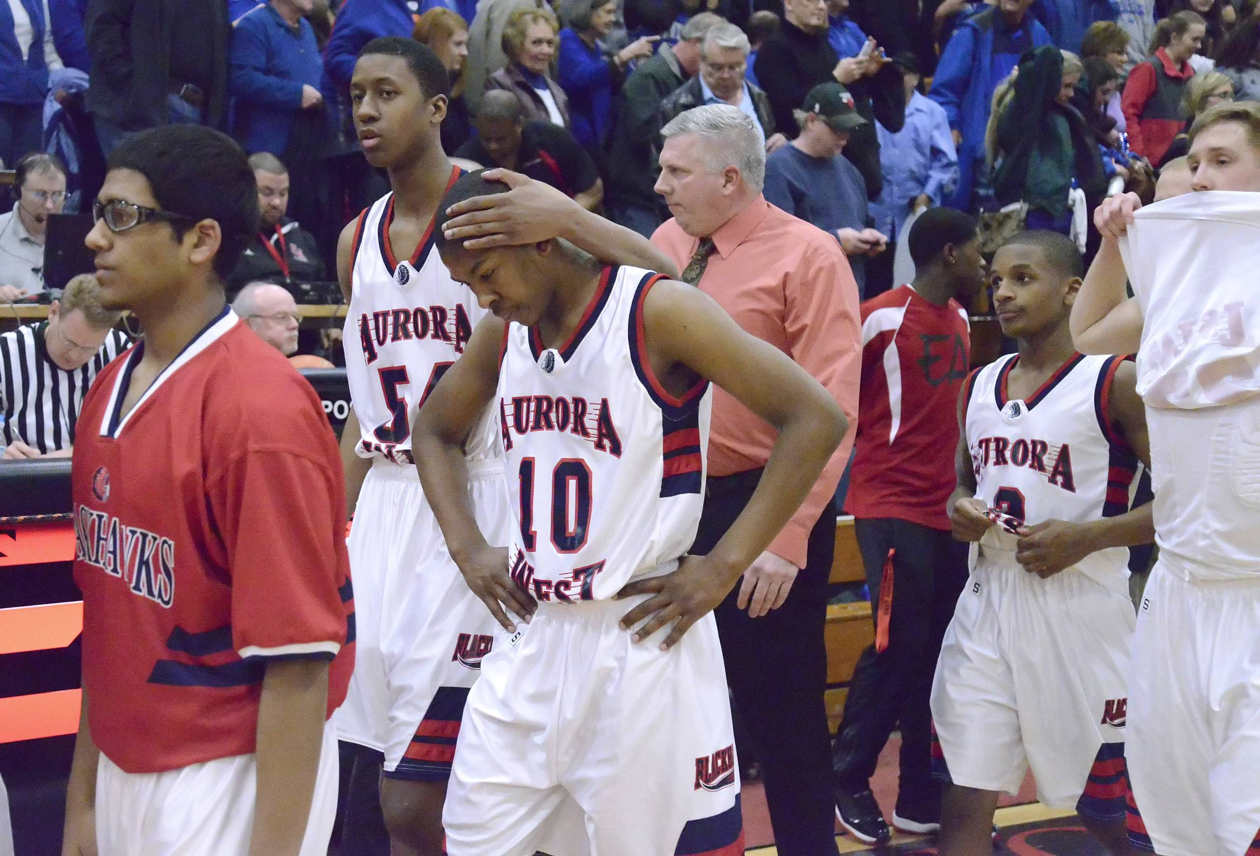 West Aurora's Carleton Williams, left, holds the head of teammate Jontrell Walker as they exit the court.