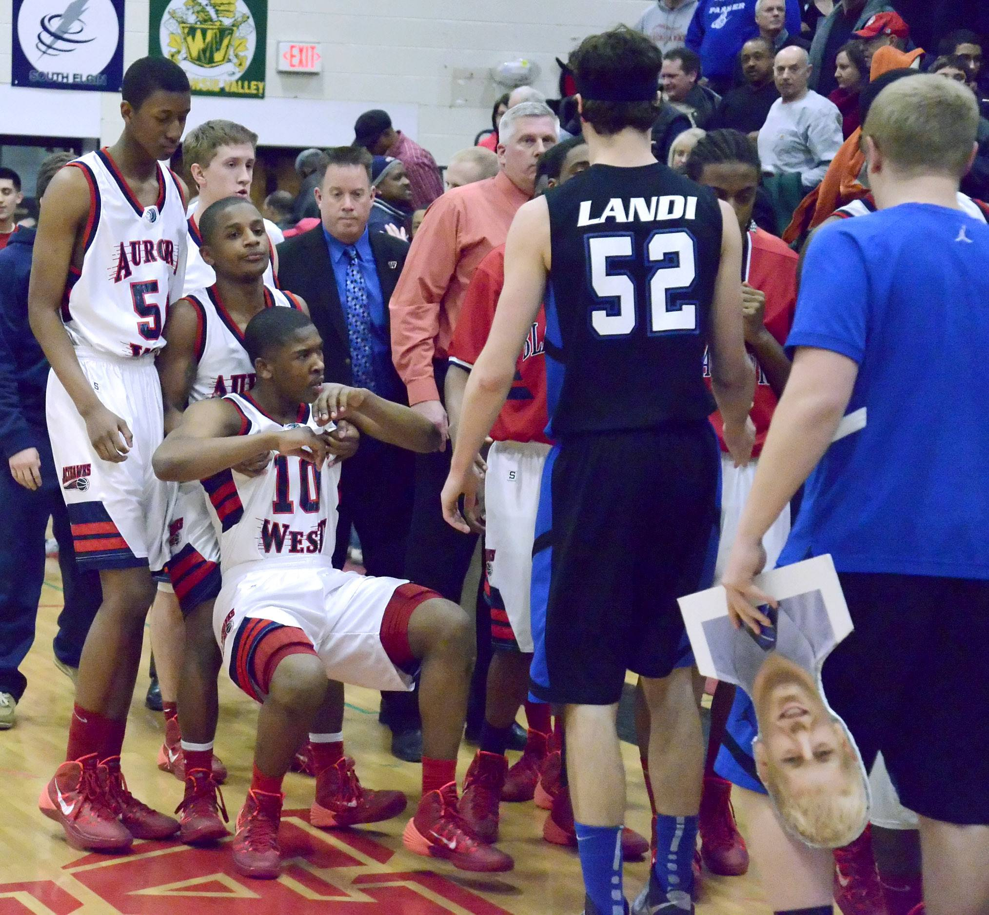 West Aurora's Matthew Dunn lifts teammate Jontrell Walker off the court after their loss to Geneva.