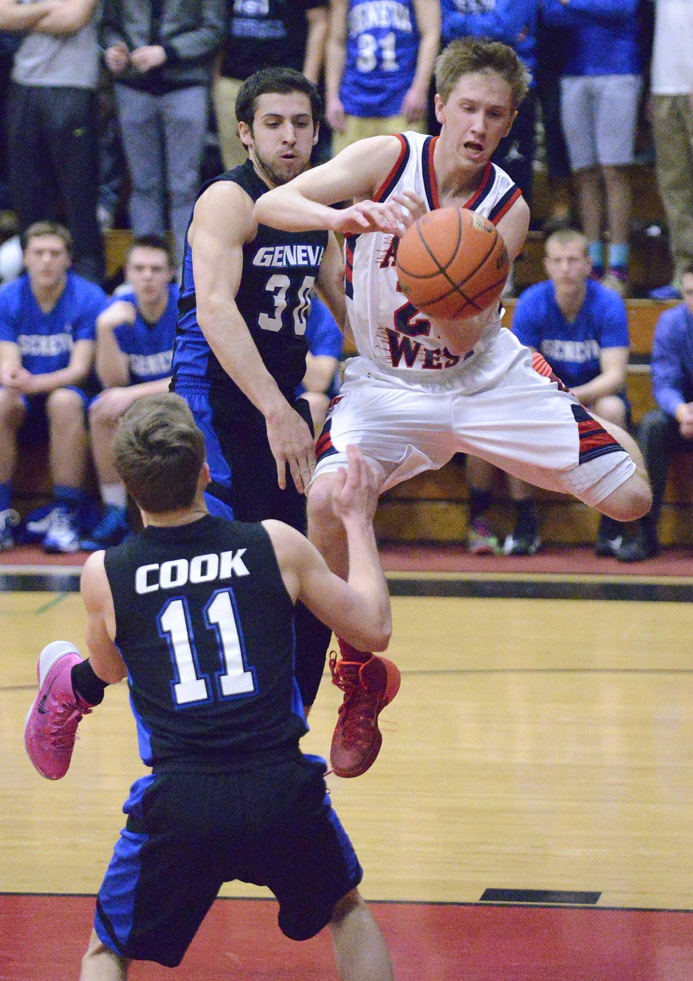 West Aurora's Tommy Koth grabs a rebound ahead of Geneva's Cameron Cook and Christopher Parrilli in the first quarter.