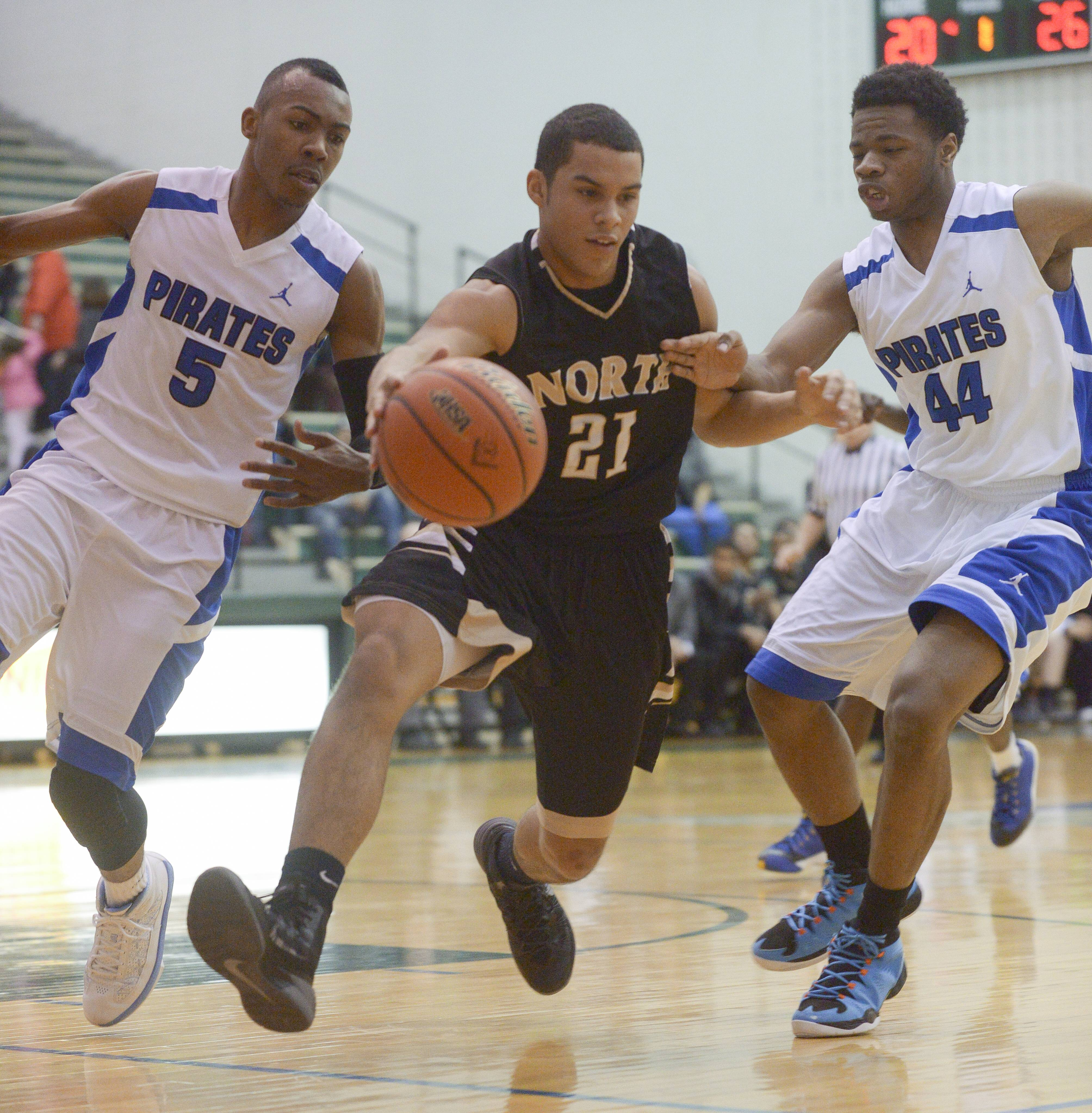 Glenbard North's Kendall Holbert drives the ball through Proviso East's Jevon Carter and Josh Smith.