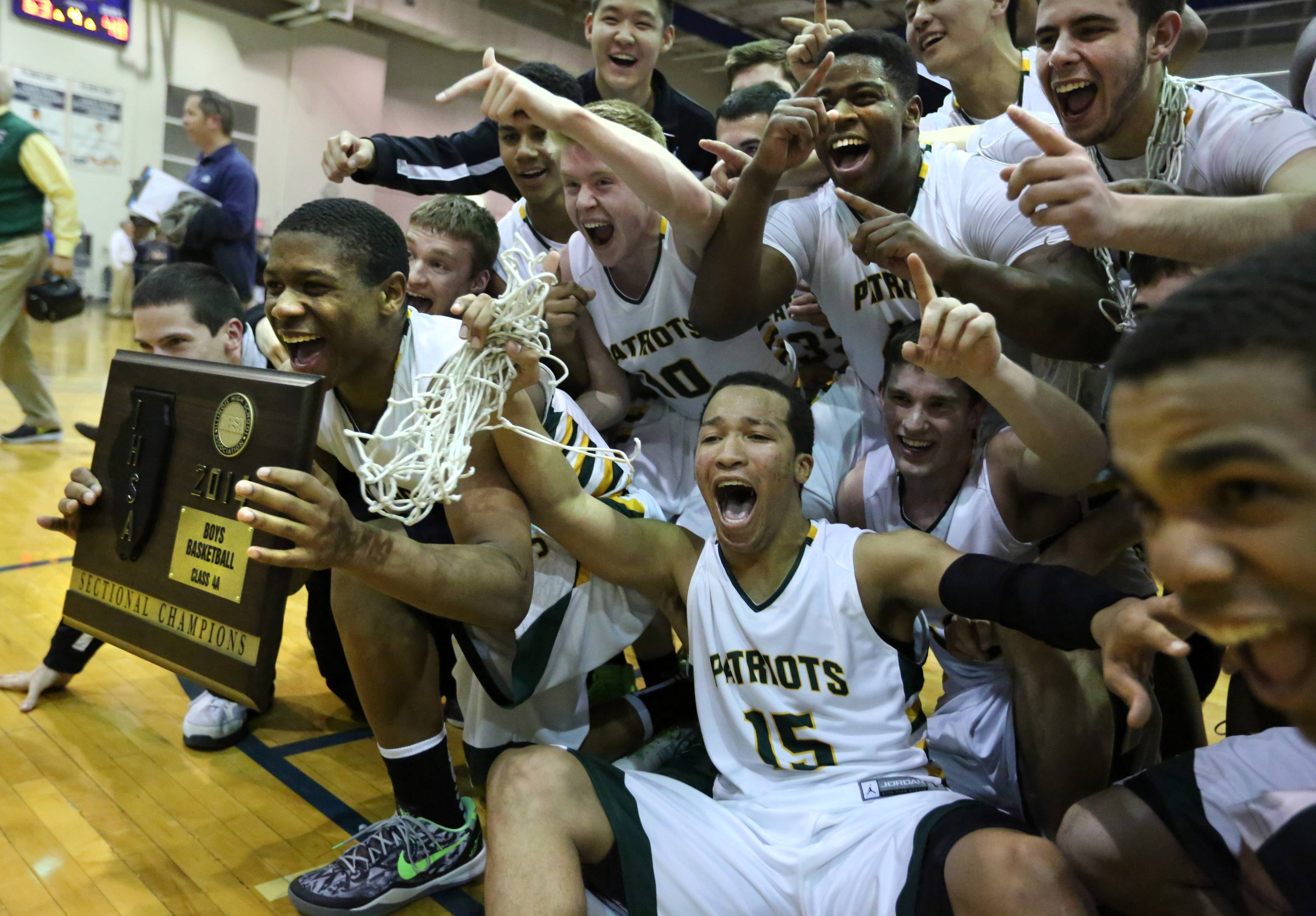 Stevenson's Matt Johnson, holding plaque, and Jalen Brunson, middle, celebrate after winning the Class 4A sectional final over Fremd on Friday in Lake Zurich.