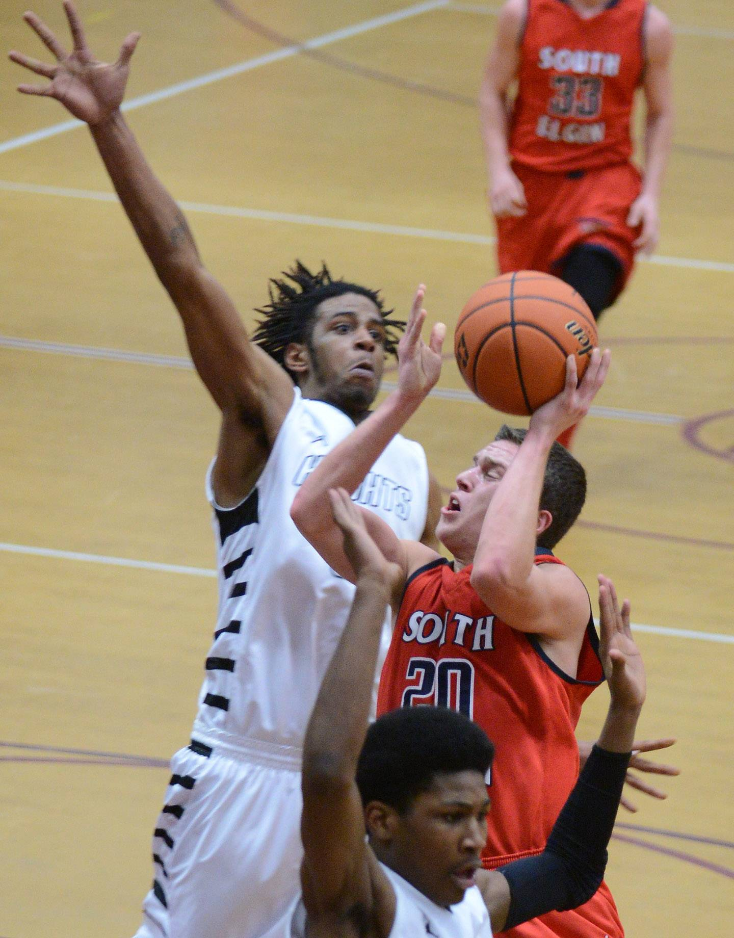 South Elgin's Matt McClure (20) is about to have his shot blocked by Rockford Auburn's Nylek Cobb (5) during Friday's Class 4A Elgin sectional final.