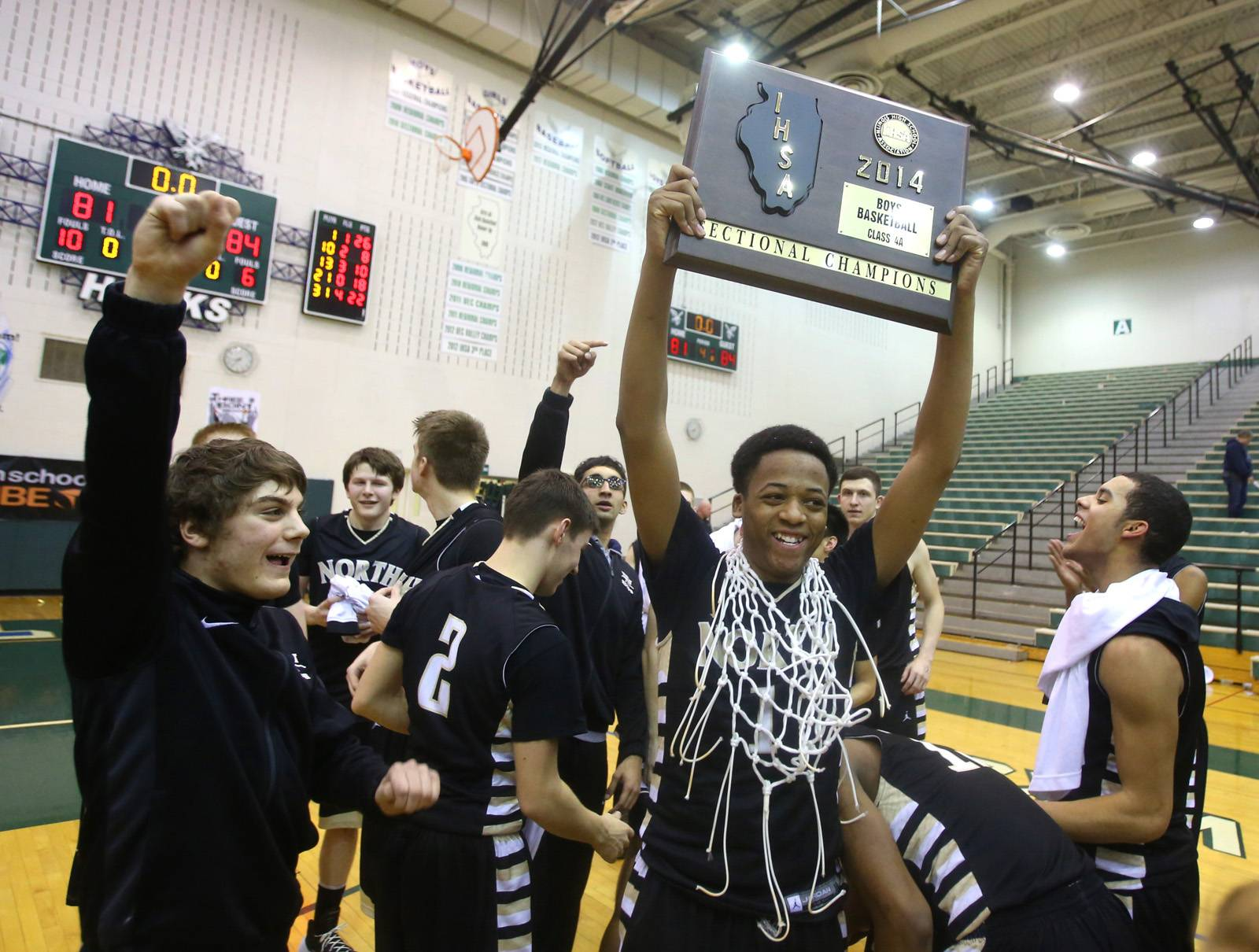 Glenbard North's Jeremiah Fleming hoists the Bartlett boys basketball sectional championship plaque.