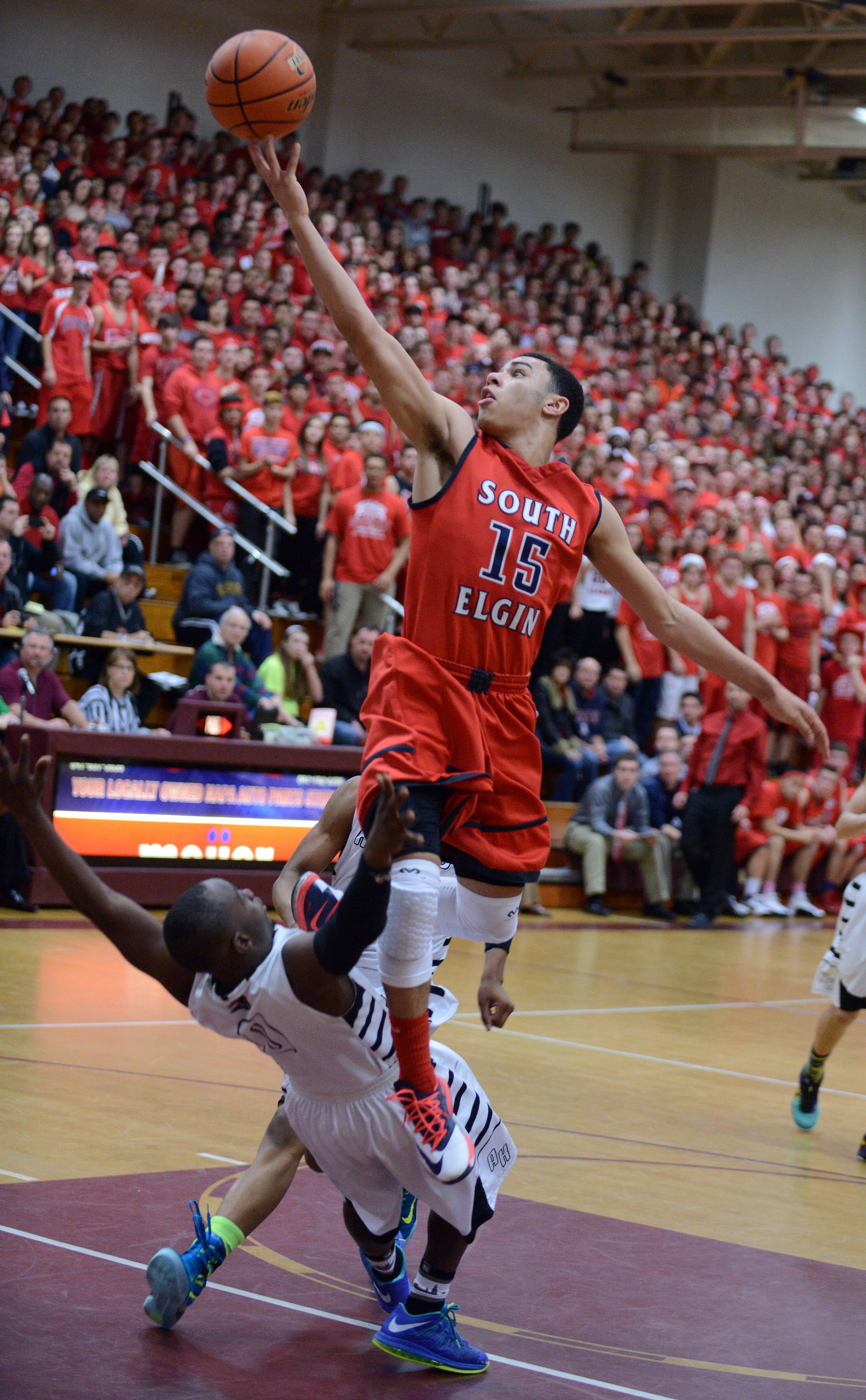 South Elgin's Matthew Smith  glides to the basket and draws a blocking call against Rockford Auburn's Phil Trammell.