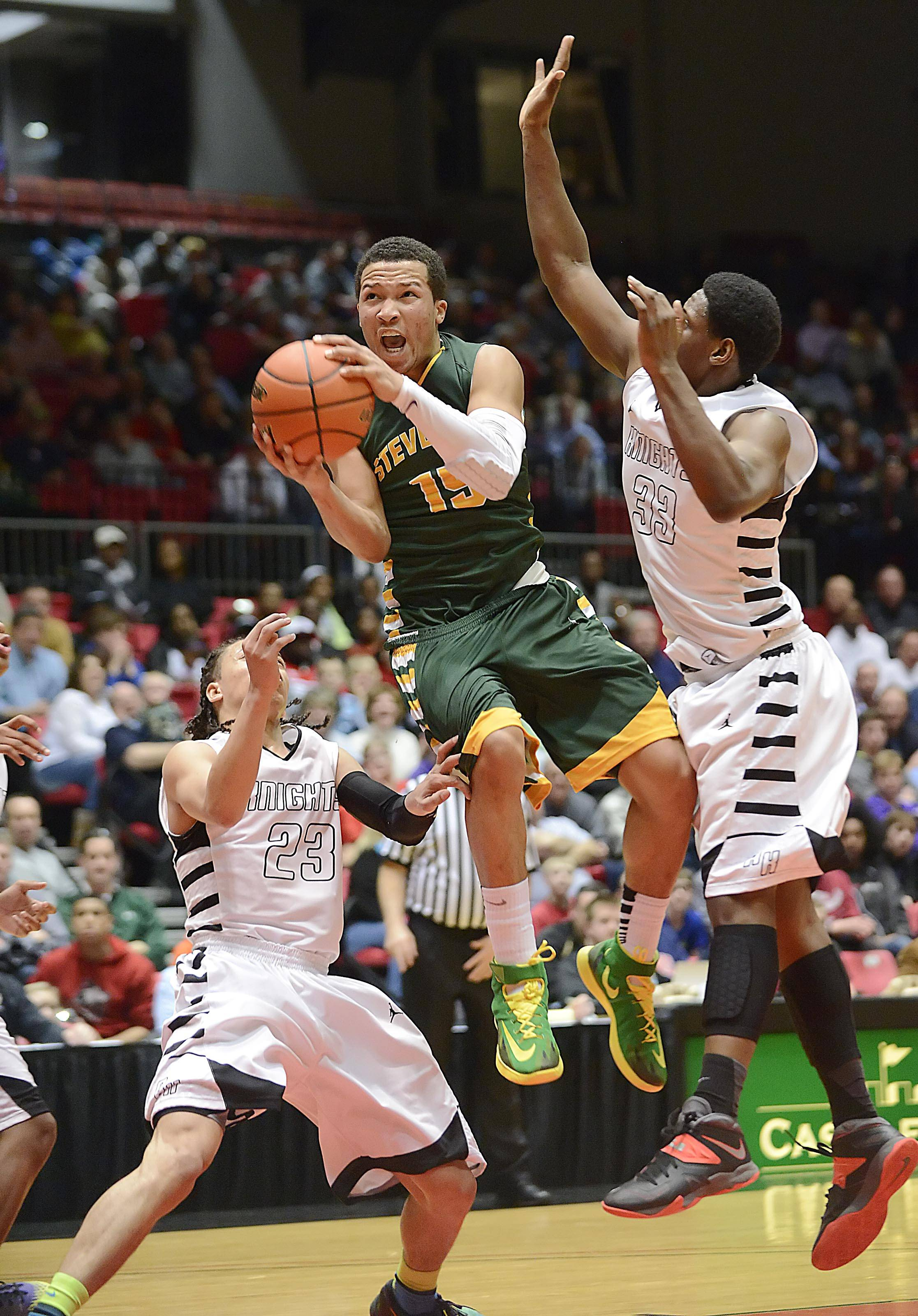 Stevenson's Jalen Brunson splits the defense of Rockford Auburn's Laytwan Porter and Malik Minor, right, in the Class 4A Northern Illinois University supersectional Tuesday.