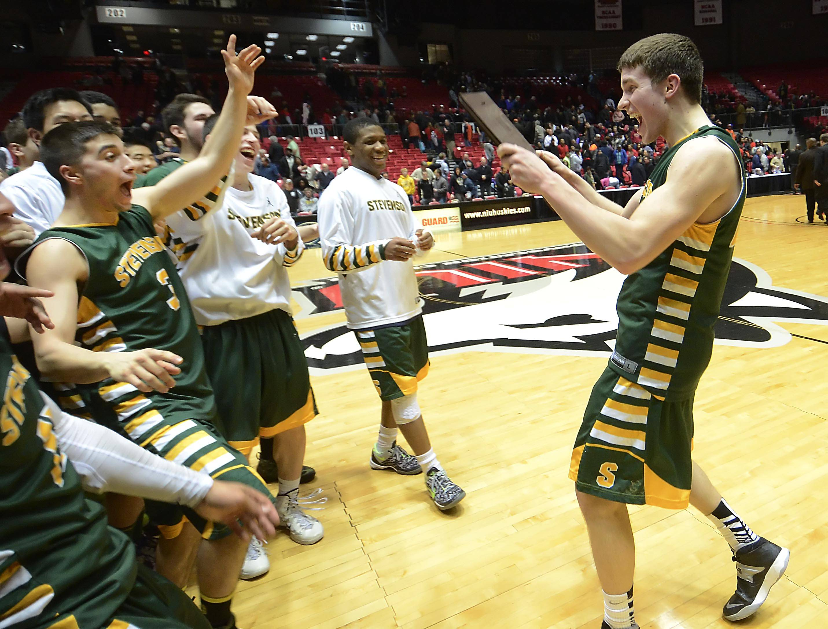 Stevenson's Matt Morrissey brings the championship plaque to his teammates after defeating Rockford Auburn in the Class 4A Northern Illinois University supersectional Tuesday.