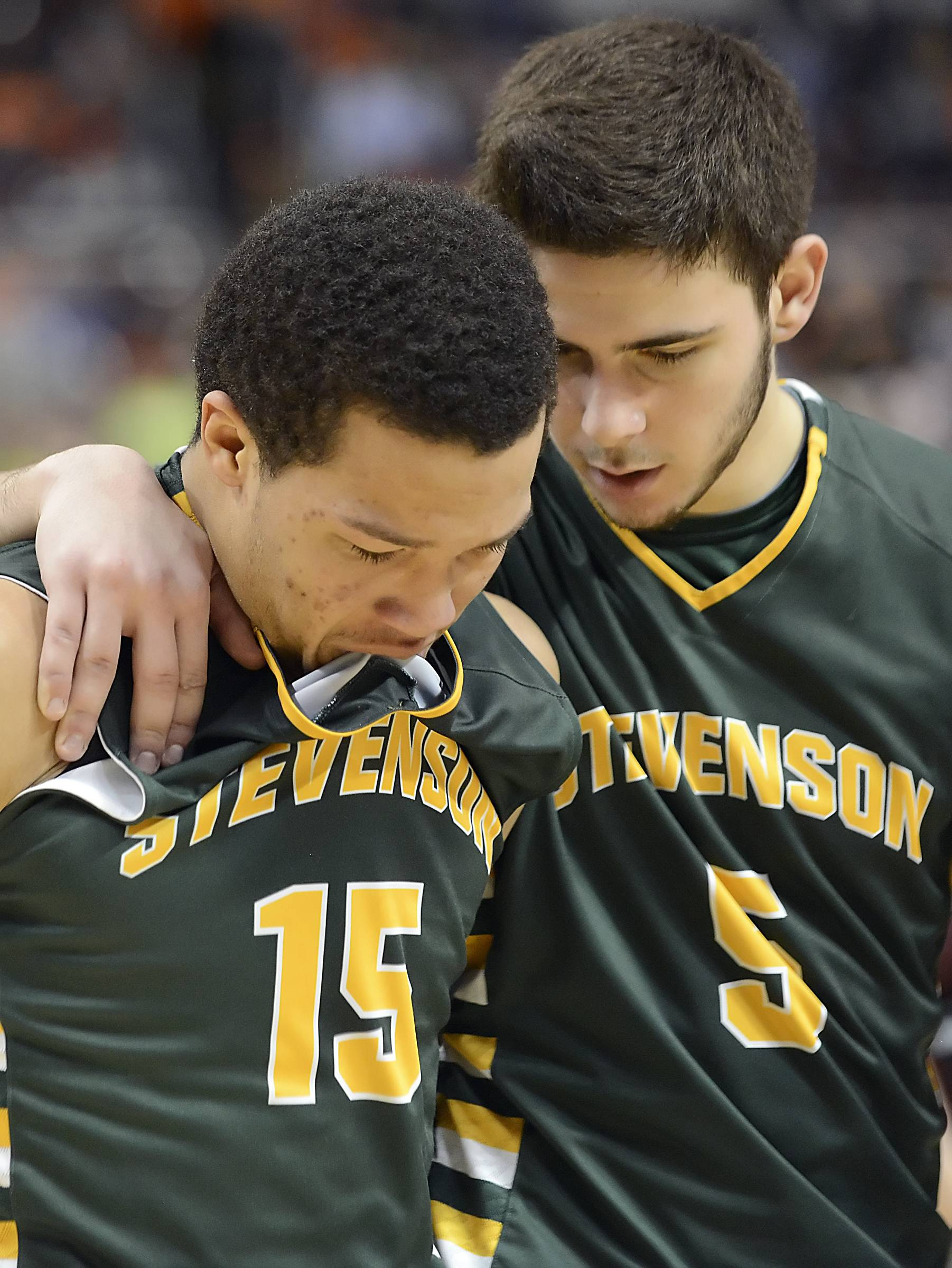 Stevenson's Jalen Brunson bites his jersey while walking off the court with teammate Parker Nichols after the Patriots lost to Whitney Young in the Class 4A state semifinals at Carver Arena in Peoria on Friday.