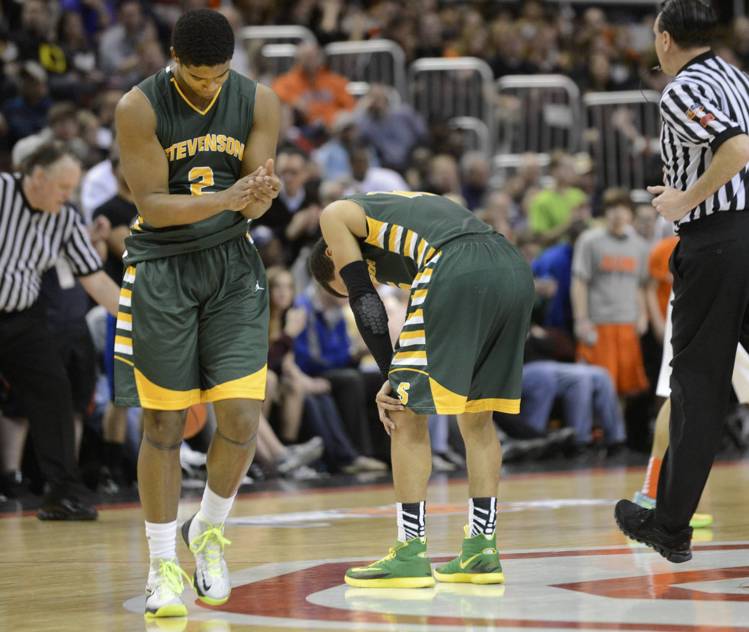 Stevenson's Jalen Brunson puts his hands on his knees as teammate Cameron Green walks off the floor following a Class 4A state semifinal loss to Whitney Young at Carver Arena in Peoria.