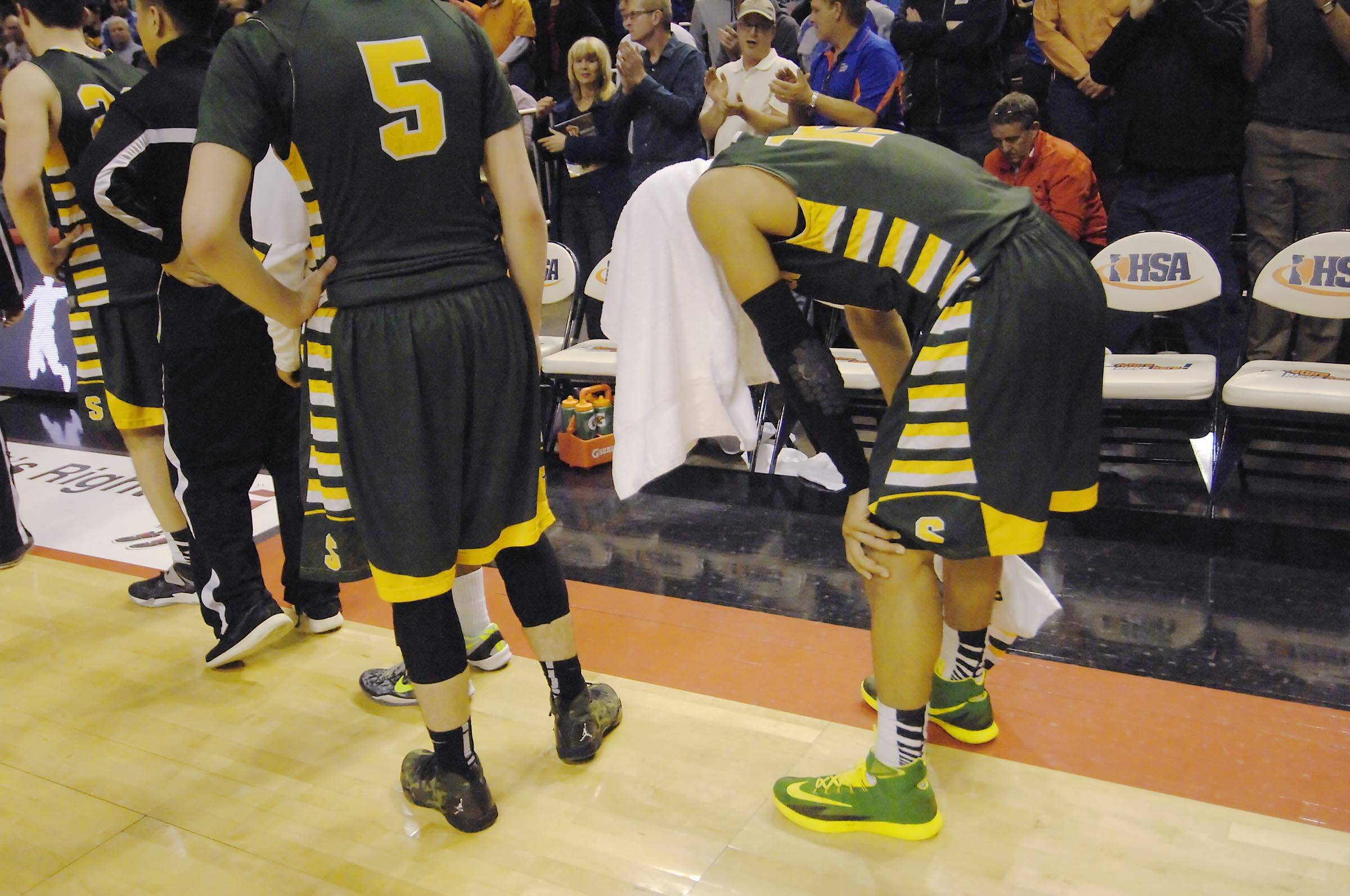 Stevenson's Jalen Brunson covers his head with a towel after the Patriots lost to Whitney Young in the Class 4A state semifinals at Carver Arena in Peoria Friday.