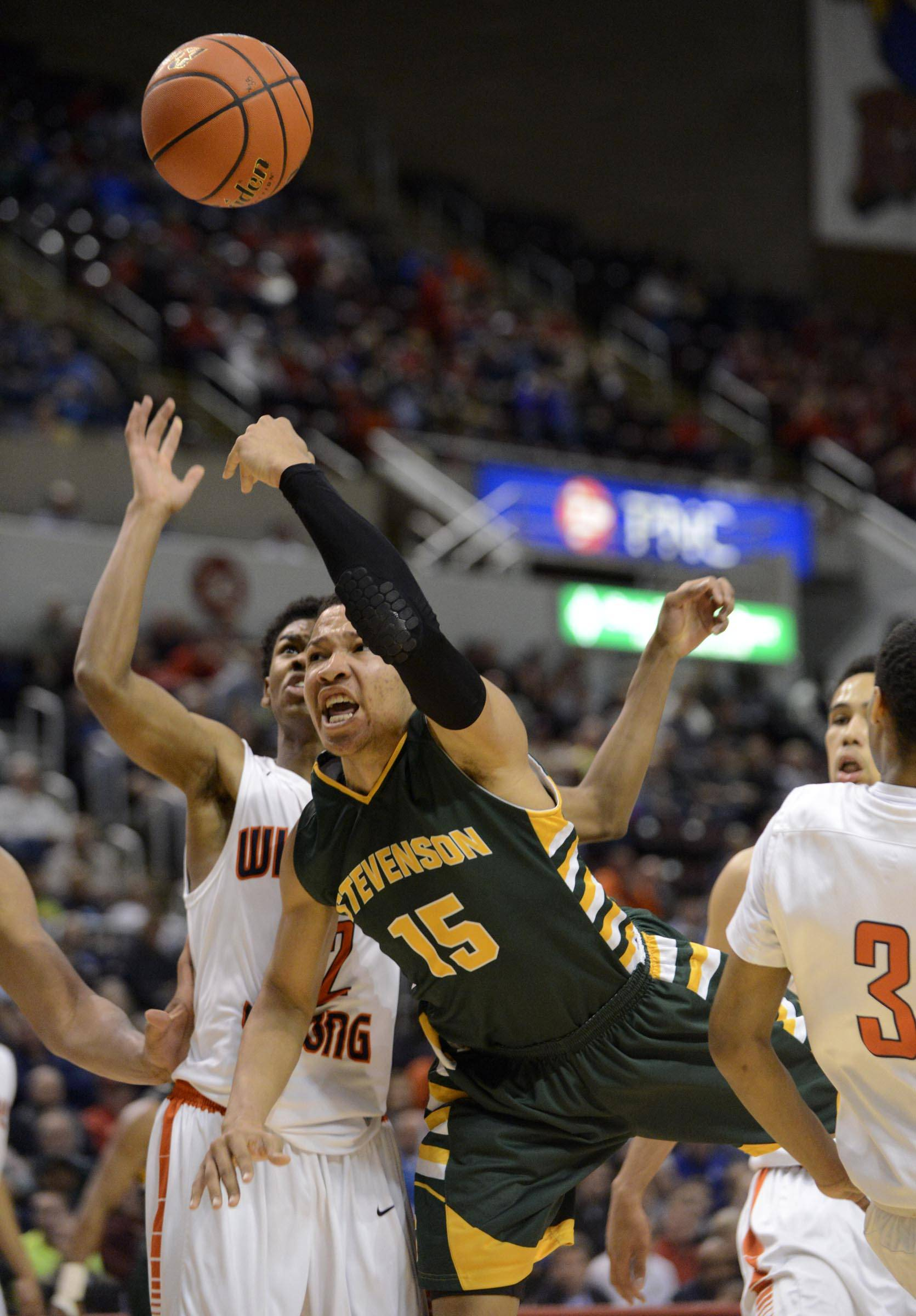 Stevenson's Jalen Brunson tosses up the ball as he is fouled by Whitney Young's Erwin Henry in the Class 4A state semifinals at Carver Arena in Peoria on Friday.