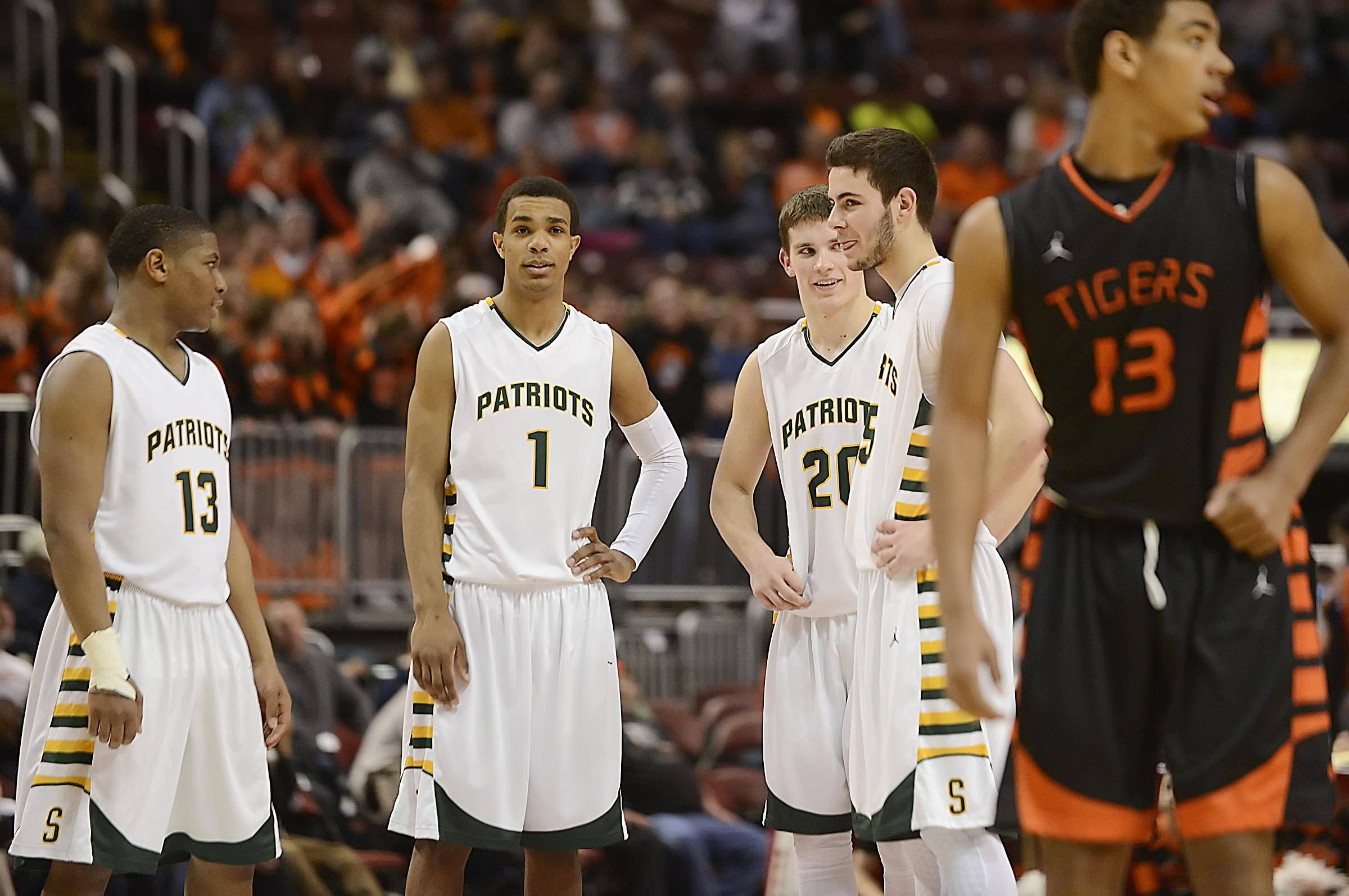 Stevenson's Matt Johnson, Connor Cashaw, Matt Morrissey, and Parker Nichols begin to relax in the final minutes of the Patriots' win over Edwardsville in the Class 4A third-place game at Carver Arena in Peoria on Saturday.